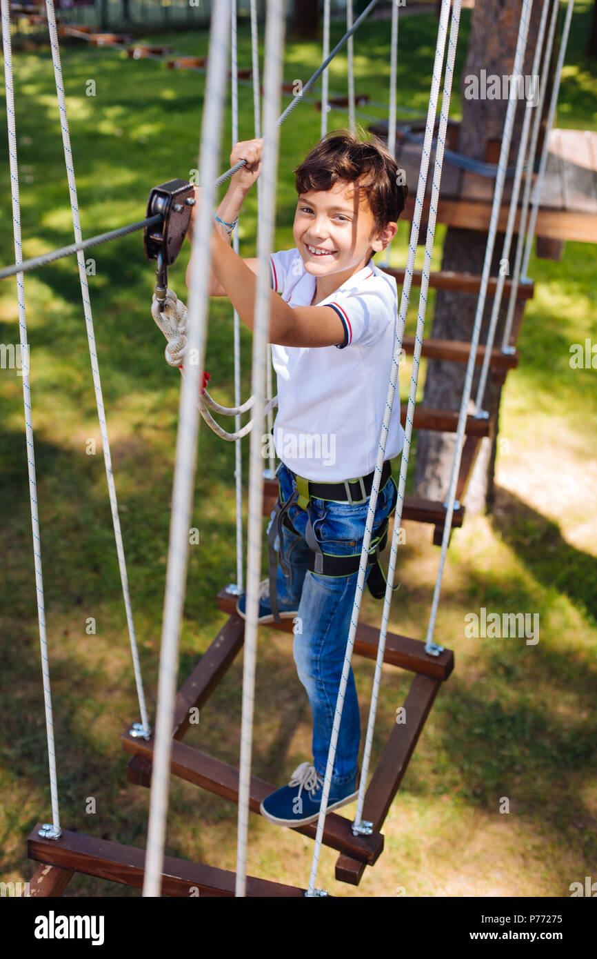 Happy preteen boy standing on swing at rope park - Stock Image