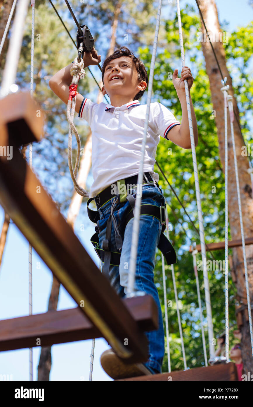 Pleasant preteen boy making steps along rope trail - Stock Image
