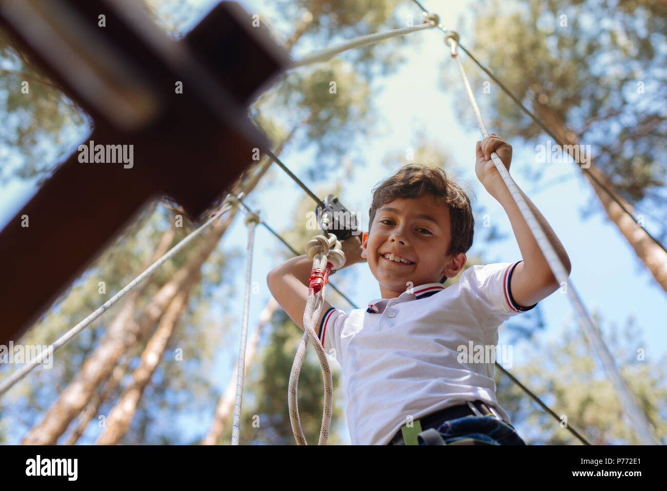 Upbeat preteen boy smiling from rope park trial - Stock Image