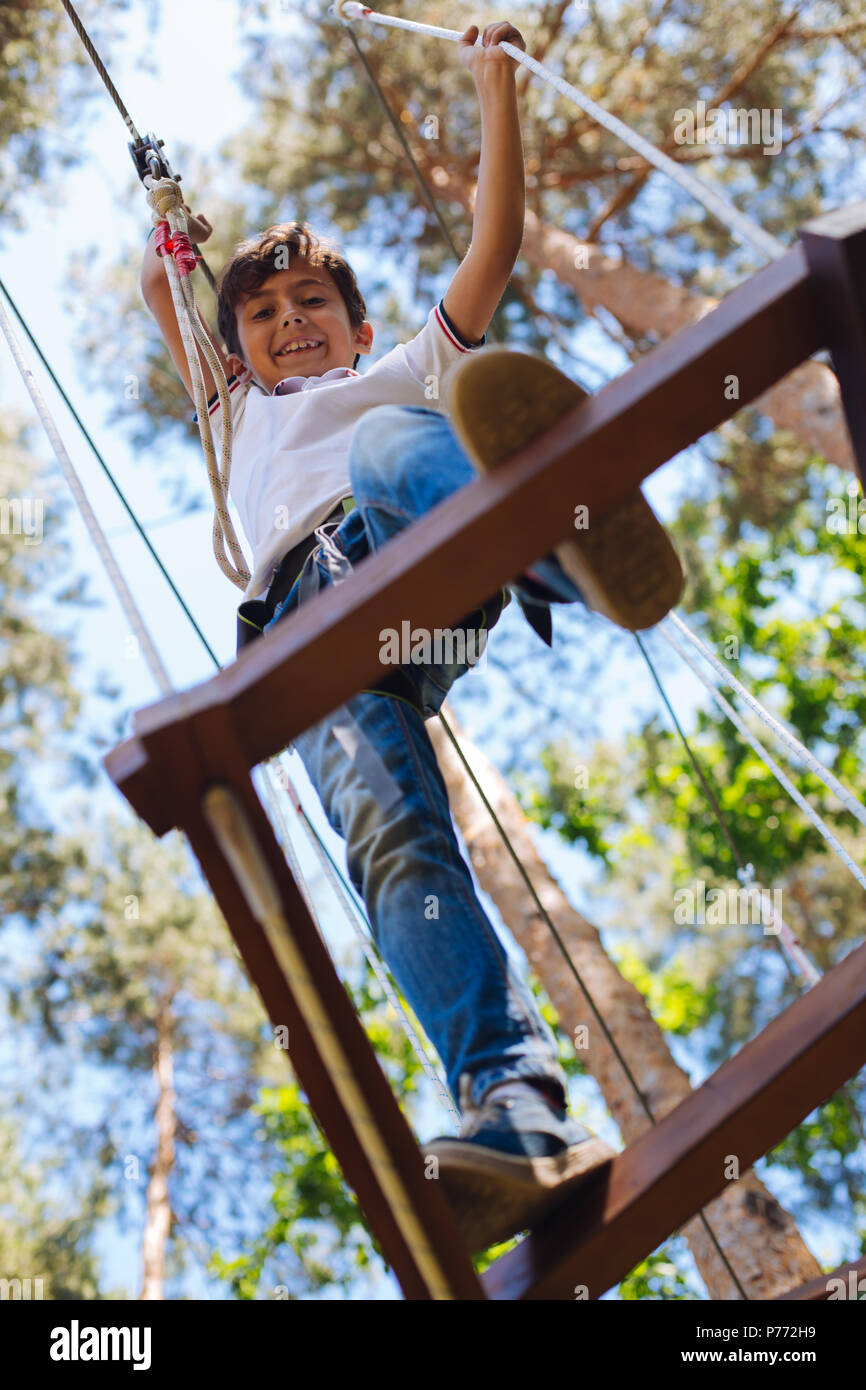 Cheerful preteen boy making step while climbing at rope park - Stock Image
