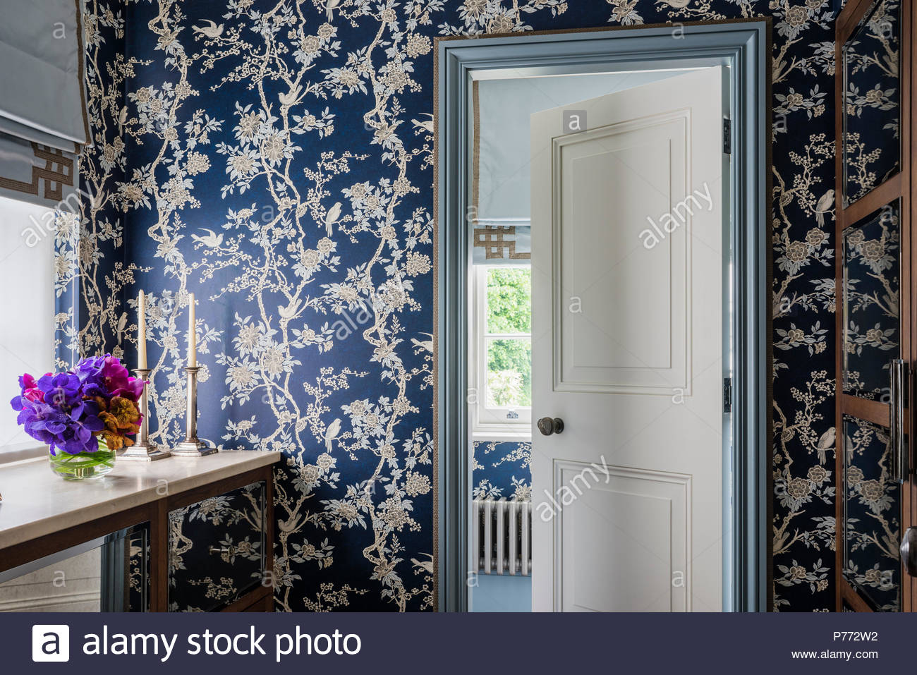 cut flowers at window cabinet with dark blue and gold oriental style