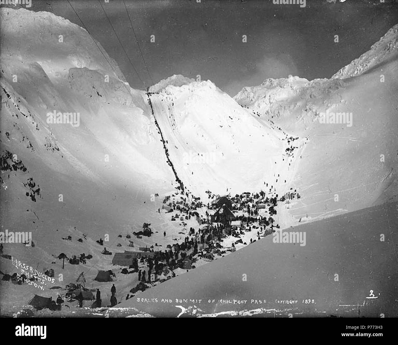 . English: Klondikers at The Scales, ascending the Chilkoot Pass, Alaska, 1898. English: Shows the alternative route Pederson Pass to the right. Pederson Pass may also have been known as Peterson Pass . Caption on image: 'Scales and summit of Chilkoot Pass 1898' Original photograph by Eric A. Hegg 190A; copied by Larss and Duclos . Klondike Gold Rush. Subjects (LCTGM): Tents--Alaska--Chilkoot Pass Subjects (LCSH): Chilkoot Trail; Trails--Alaska; Chilkoot Pass (Alaska); Pederson Pass; Mountain passes--Alaska  . 1898 7 Klondikers at The Scales, ascending the Chilkoot Pass, Alaska, 1898 (HEGG 725 - Stock Image