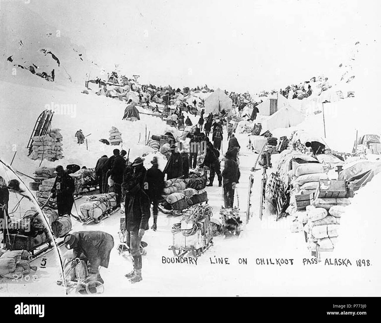 . English: Klondikers waiting in line for customs, Chilkoot Pass, Alaska, ca. 1898. English: Shows Klondikers waiting to be checked by customs and the North West Mounted Police at the Canada - United States boundry line . Caption on image: 'Boundry line on Chilkoot Pass, Alaska' Similiar to Hegg 236 with caption: 'Chilkoot Summit, March 1898' . Klondike Gold Rush. Subjects (LCTGM): Sleds & sleighs--Alaska--Chilkoot Pass; Tents--Alaska--Chilkoot Pass Subjects (LCSH): Chilkoot Pass (Alaska); Mountain passes--Alaska; Chilkoot Trail; Trails--Alaska; North West Mounted Police (Canada)  . circa 1898 - Stock Image