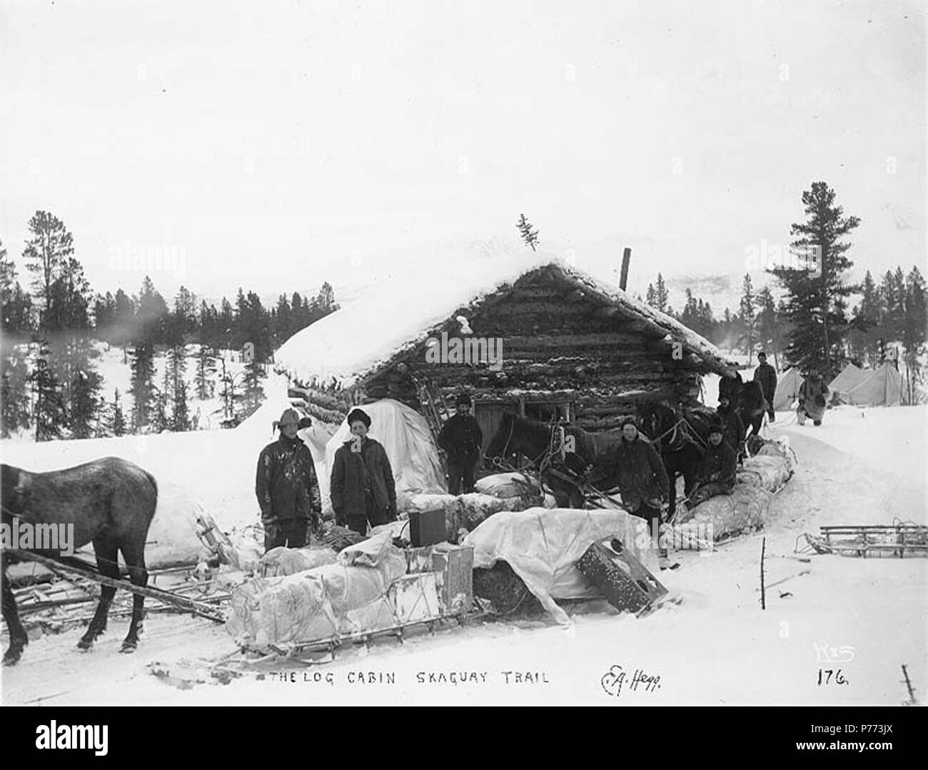 . English: Klondikers with horse drawn sleds resting at a log cabin, White Pass Trail, ca. 1898. English: Possibly site of Log Cabin, British Columbia . Caption on image: 'The Log Cabin Skaguay Trail' Original image in Hegg Album 8, page 32 . Original photograph by Eric A. Hegg 176; copied by Webster and Stevens 176.A . Klondike Gold Rush. Subjects (LCTGM): Log cabins--British Columbia; Sleds & sleighs--British Columbia; Tents--British Columbia Subjects (LCSH): White Pass Trail; Trails--British Columbia  . circa 1898 7 Klondikers with horse drawn sleds resting at a log cabin, White Pass Trail, - Stock Image