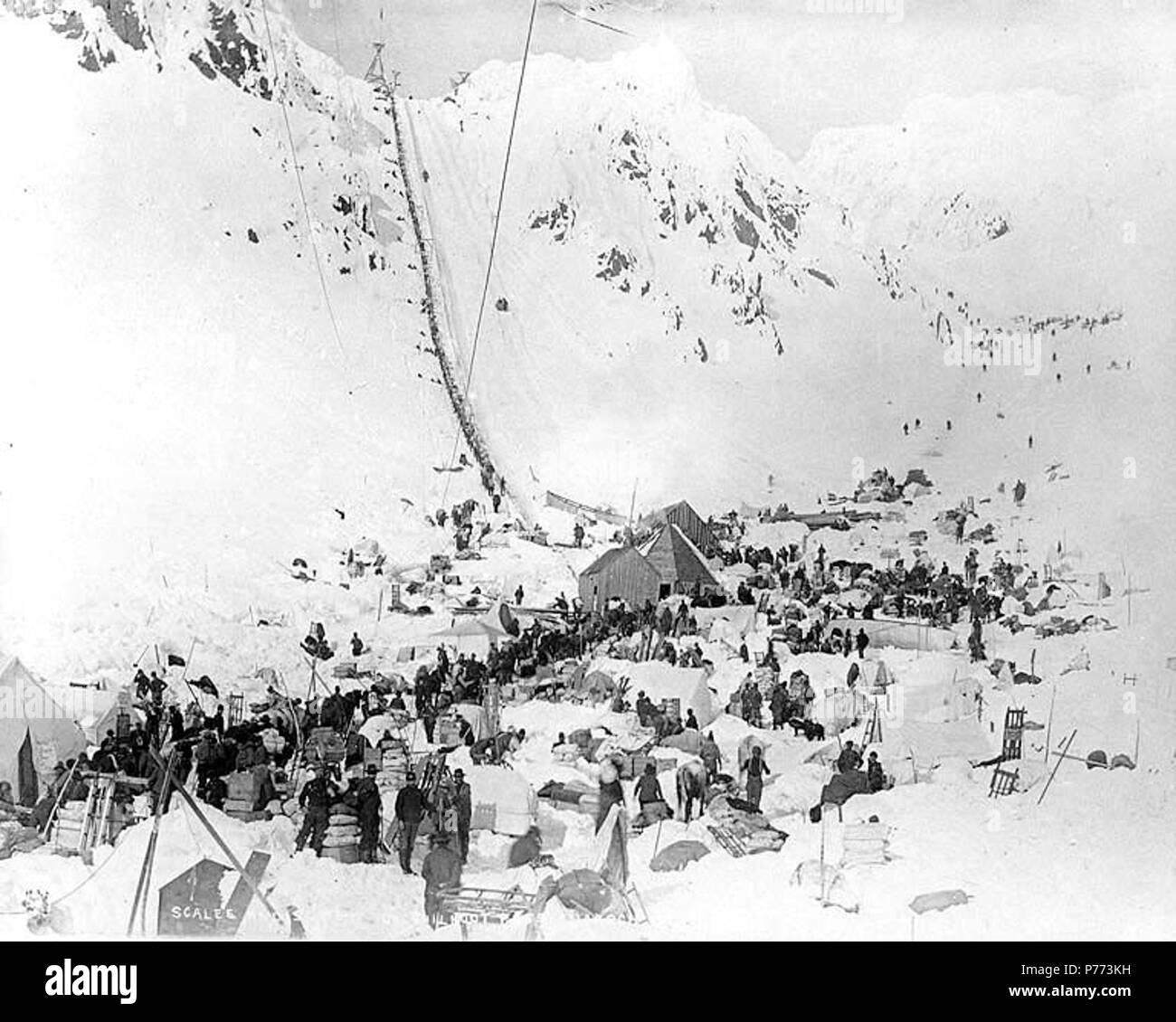 . English: Klondikers with supplies at The Scales preparing to ascend to the summit of Chilkoot Pass, Alaska, March 1898. English: Shows boat at the base of line of packers in the background . Caption on image: 'Scales and summit of Chilkoot Pass March' Klondike Gold Rush. Subjects (LCTGM): Tents--Alaska--Chilkoot Pass; Sleds--Alaska--Chilkoot Pass; Canoes--Alaska--Chilkoot Pass Subjects (LCSH): Chilkoot Trail; Trails--Alaska; Chilkoot Pass (Alaska); Mountain passes--Alaska  . 1898 7 Klondikers with supplies at The Scales preparing to ascend to the summit of Chilkoot Pass, Alaska, March 1898 ( - Stock Image