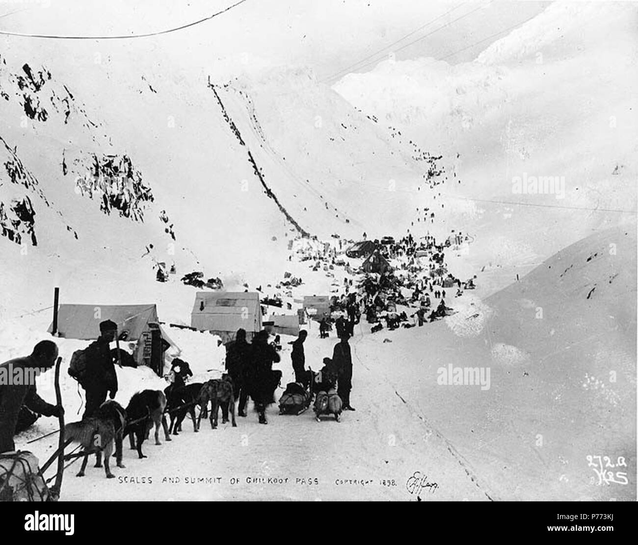 . English: Klondikers with supplies at The Scales, preparing to ascend to the summit of Chilkoot Pass, Alaska, March 1898. English: Caption on image: 'Scales and summit of Chilkoot Pass March 1898' Original image in Hegg Album 1, page 29 . Original photograph by Eric A. Hegg 105A; copied by Webster and Stevens 292.A Subjects (LCTGM): Sleds & sleighs--Alaska--Chilkoot Pass; Sled dogs--Alaska--Chilkoot Pass Subjects (LCSH): Chilkoot Trail; Trails--Alaska; Chilkoot Pass (Alaska); Mountain passes--Alaska  . Unknown date 7 Klondikers with supplies at The Scales, preparing to ascend to the summit of - Stock Image