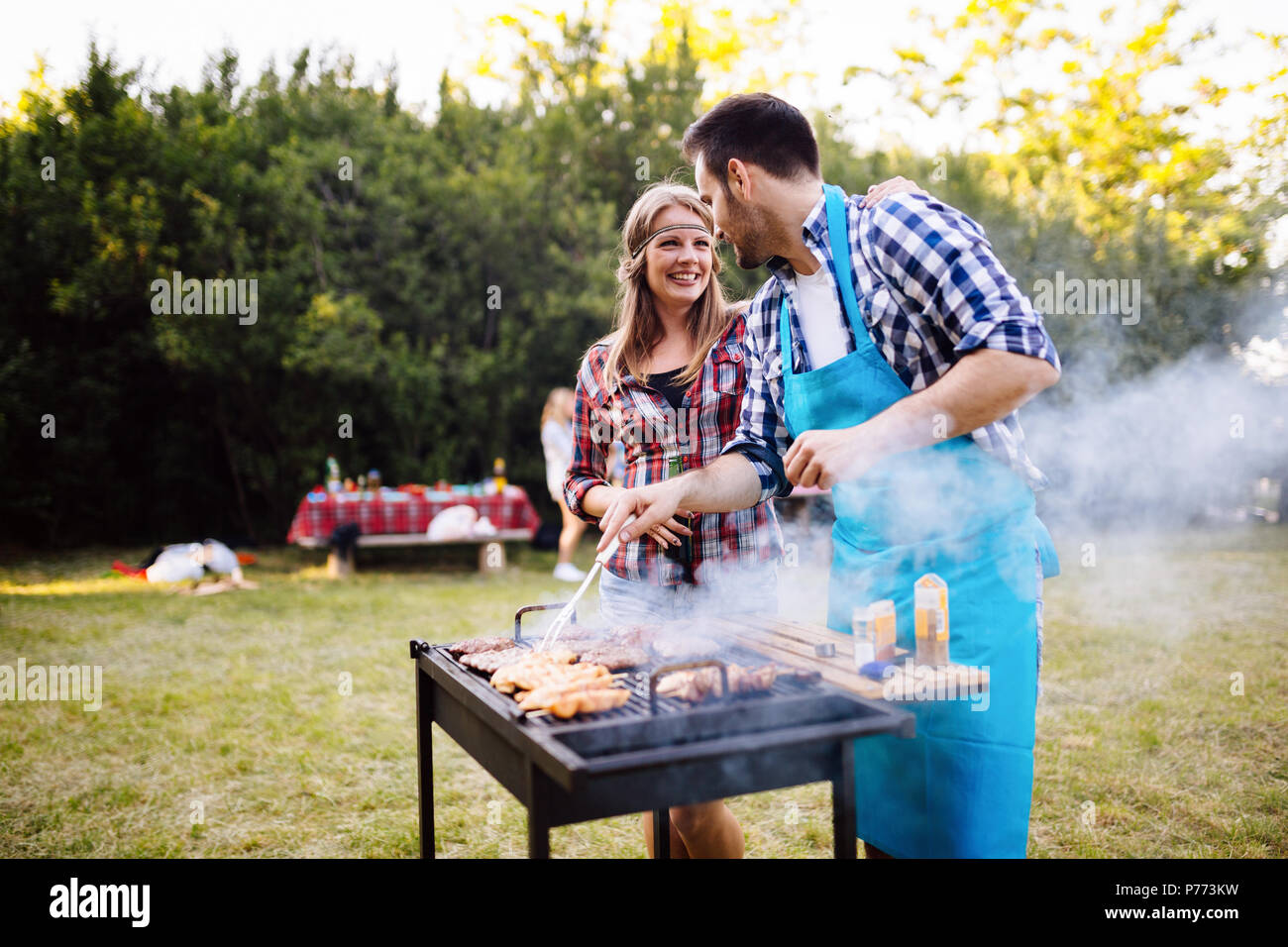 Happy students having barbecue on summer day - Stock Image