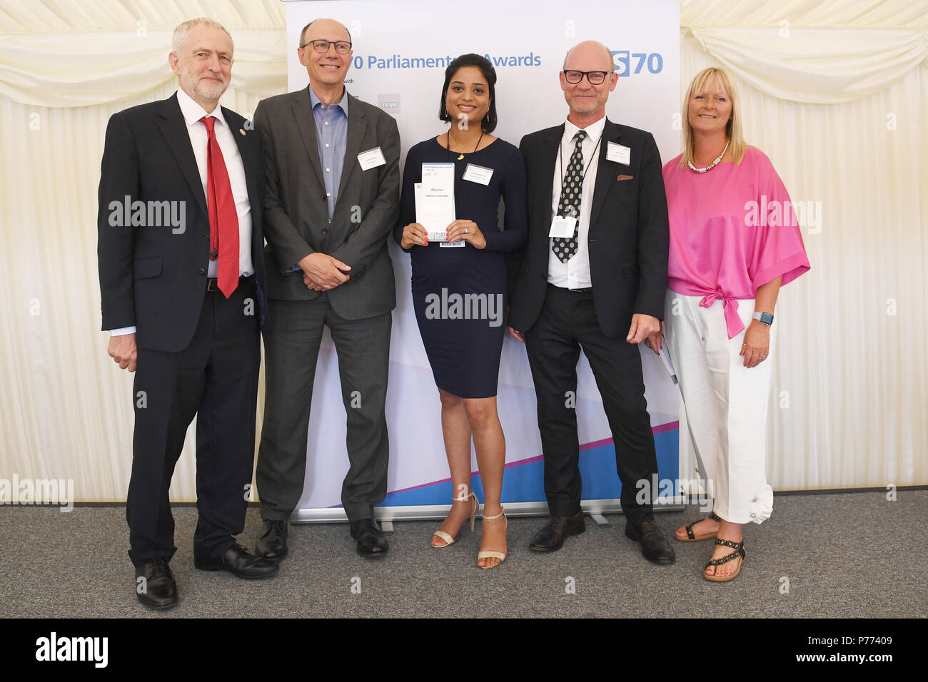 Dr Rammya Mathew (centre) and Dr Mike Clowes (second right) receive their Healthier Com unities Award from Jeremy Corbyn, Stephen Powis (second left) and Kate Smith (right) during the NHS70 parliamentary awards for the 70th anniversary of the NHS at the House of Commons in Westminster, London. - Stock Image