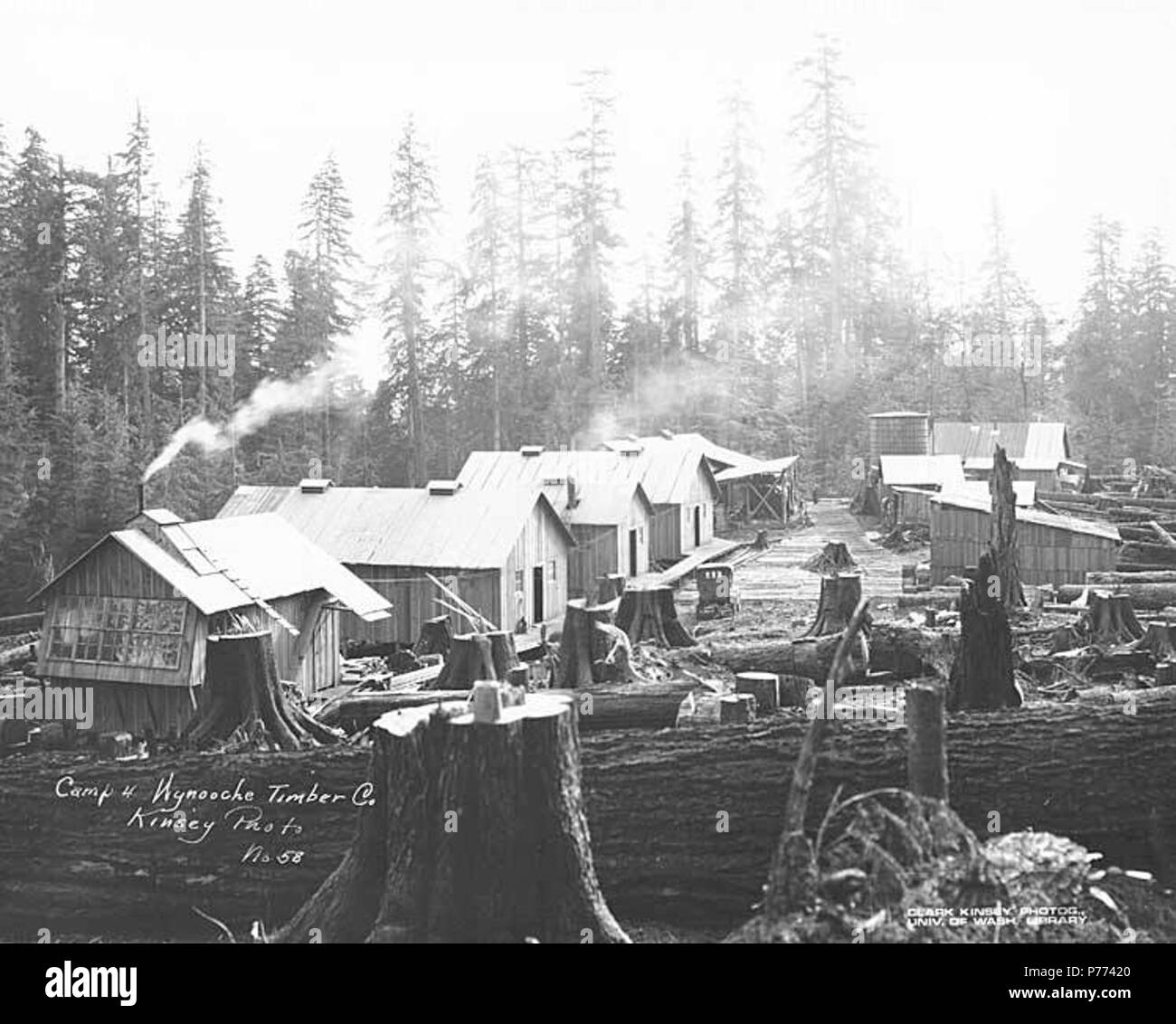 . English: Logging camp no. 4, showing saw filer's shop with windows, bunkhouses, car, and water tank, Wynooche Timber Company, ca. 1921 . English: Caption on image: Camp 4, Wynooche Timber Co. Kinsey Photo No. 58 PH Coll 516.5191 The Wynooche Timber Company began operations ca. 1913 with headquarters in Hoquiam and logging operations in Montesano. It was named for Wynooche Valley in northeast Grays Harbor County. Wynooche Timber Company was bought out by Schafer Brothers Logging Company ca. 1927. Subjects (LCTGM): Lumber camps--Washington (State); Workshops--Washington (State); Automobiles--W - Stock Image