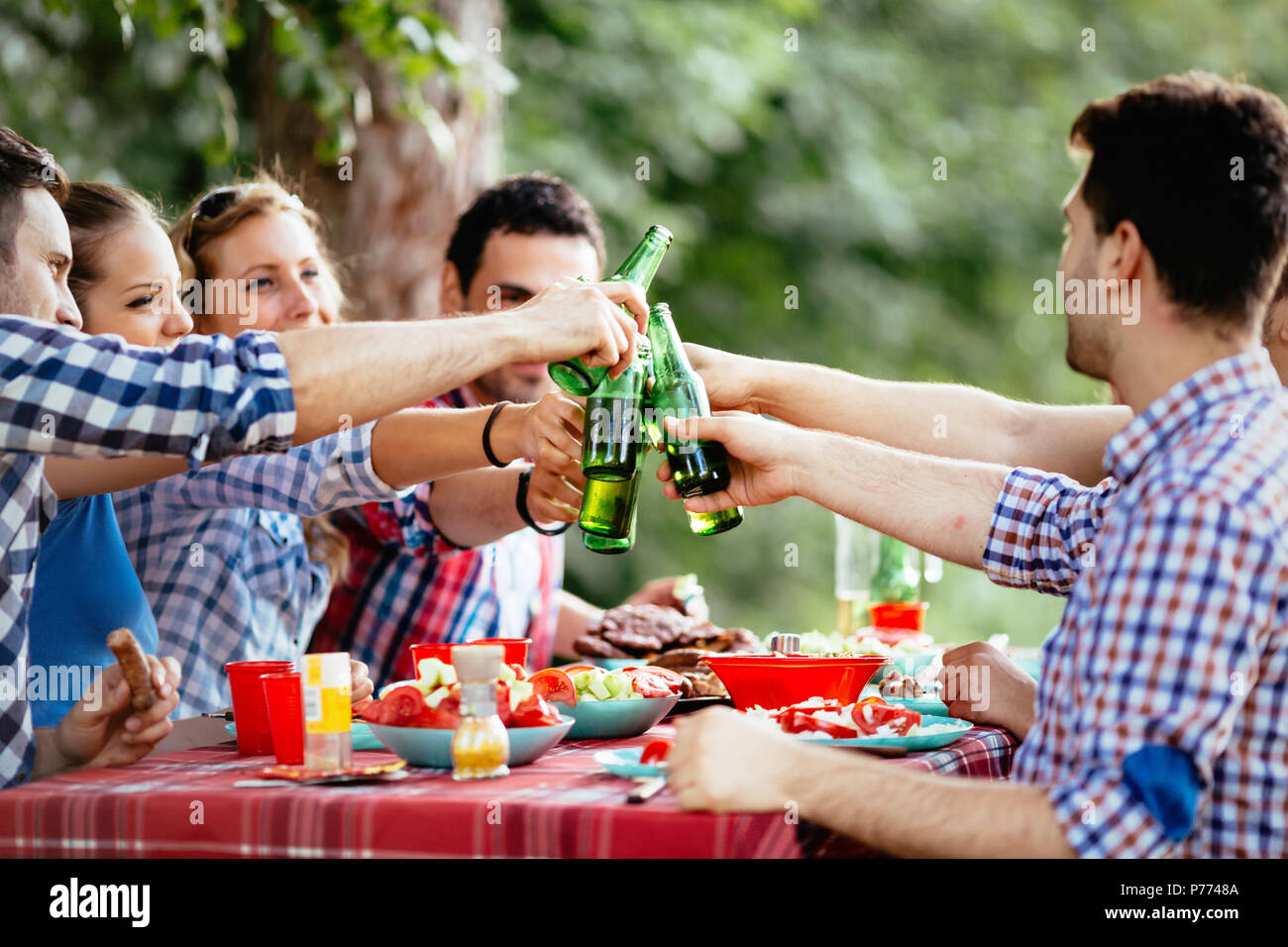 Group of happy people eating food outdoors Stock Photo