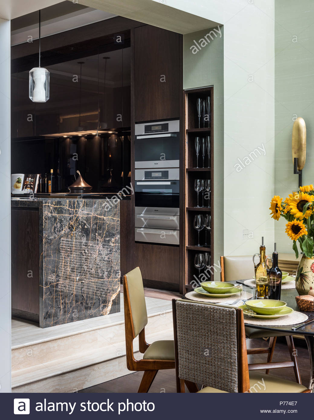 Split level kitchen in brown marble and dining room with glassware storage. - Stock Image