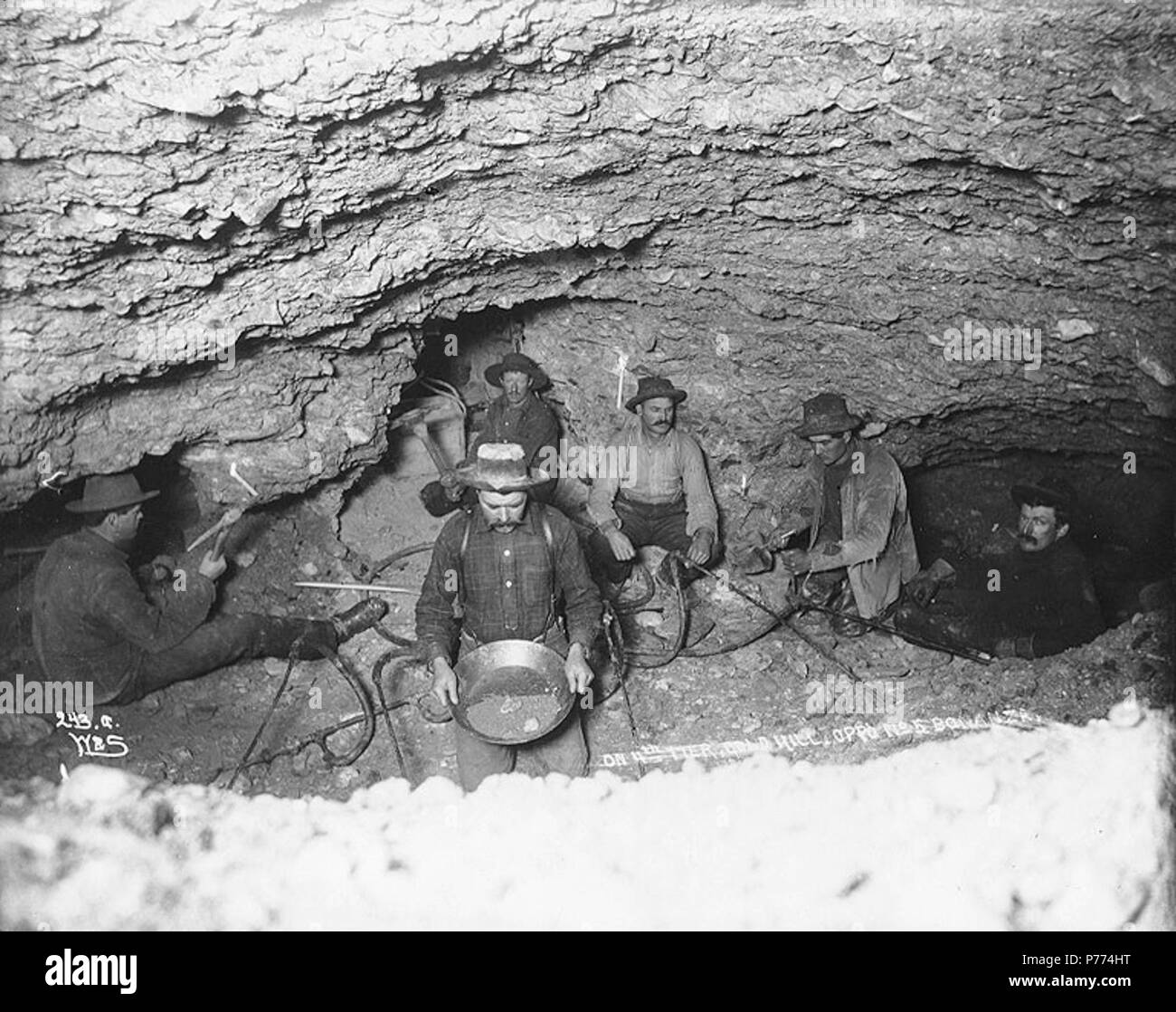 . English: Miners thawing frozen ground with steam in an underground gold mine lit by candlelight, Gold Hill, Yukon Territory, ca. 1898 . English: Shows five men using pickaxes and gold pan . Caption on image: 'On 4th tier, Gold Hill, Opp. No. 5 Bonanza.' Same as Hegg 3051 . Original image in Hegg Album 25, page 13 . Original photograph by Eric A. Hegg 778; copied by Webster and Stevens 243.A . Klondike Gold Rush. Subjects (LCTGM): Gold miners--Yukon--Gold Hill; Gold mining--Yukon--Gold Hill; Candles; Steam Subjects (LCSH): Yukon--Gold discoveries  . circa 1898 9 Miners thawing frozen ground w - Stock Image