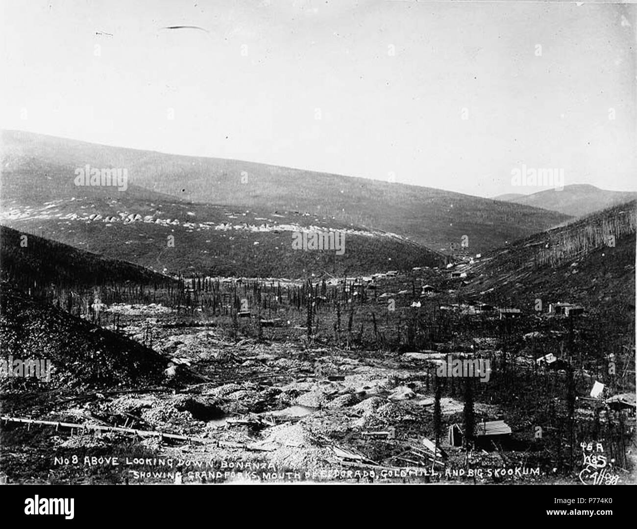 . English: Mining claim No. 8 above Bonanza Creek showing Grand Forks, mouth of Eldorado, Gold Hill, and Big Skookum, Yukon Territory, ca. 1898. English: Caption on image: 'No 8 above looking down Bonanza showing Grand Forks, mouth of Eldorado, Gold Hill, and Big Skookum' Original image in Hegg Album 24, page 33 . Original photograph by Eric A. Hegg 558; copied by Webster and Stevens 45.A . Klondike Gold Rush. Subjects (LCTGM): Gold mining--Yukon--Bonanza Creek; Mining claims--Yukon--Bonanza Creek; Rivers--Yukon Subjects (LCSH): Grand Forks (Yukon); Eldorado Creek (Yukon); Gold Hill (Yukon); B - Stock Image