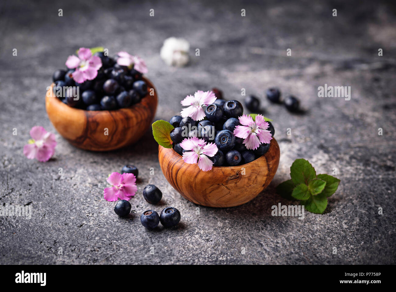 Fresh ripe blueberries in wooden bowl. Selective focus - Stock Image