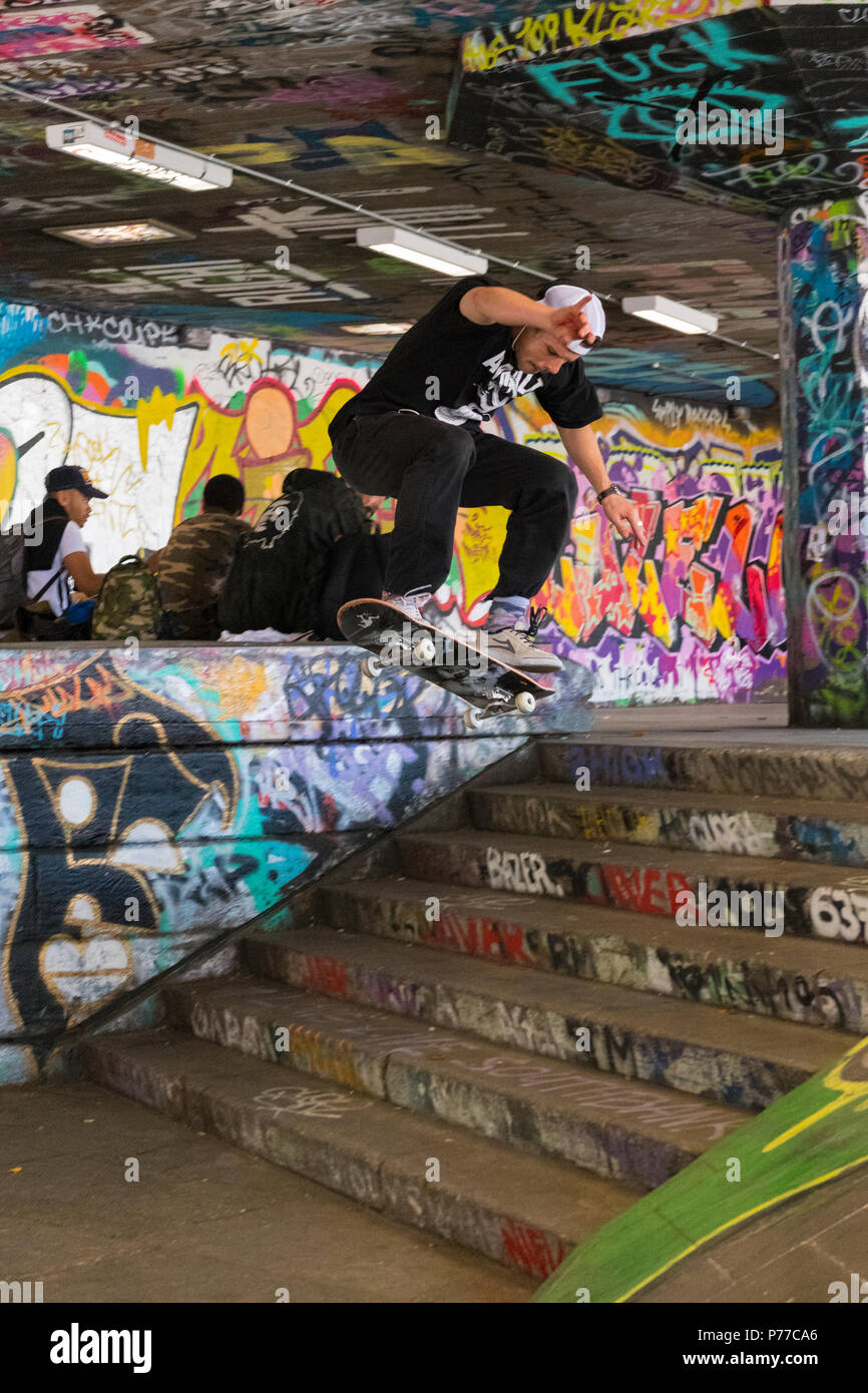 London Southbank Centre Skatepark graffiti skateboarder in air flight down stairs steps skateboarding jump trick action skill acrobatic - Stock Image
