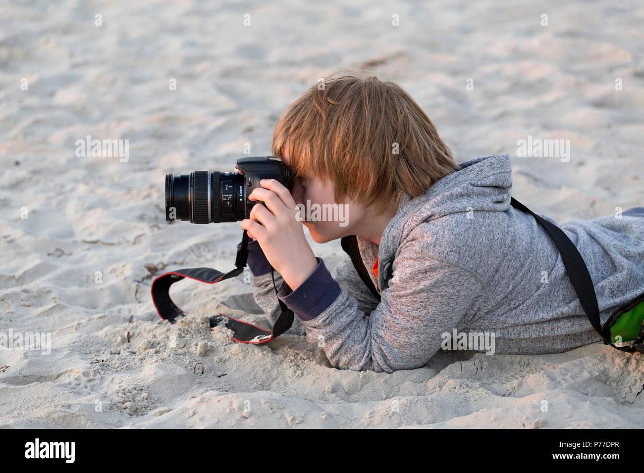 young boy taking photos at a beach - Stock Image
