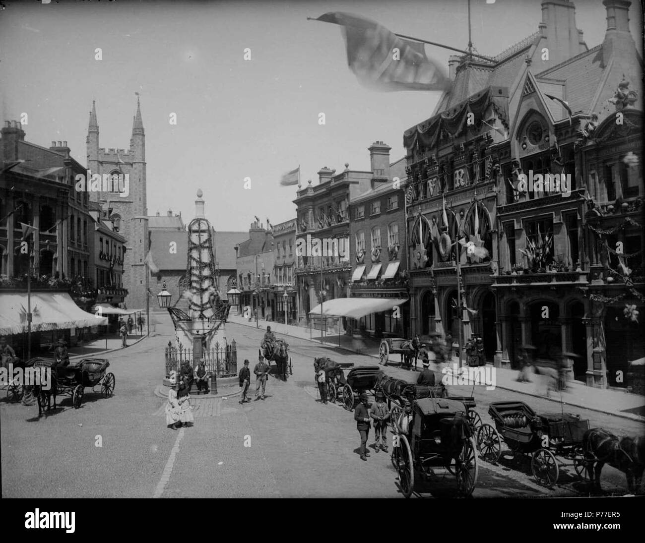 English: Market Place, Reading, looking northwards to St. Laurence's Church, 1887. The Simeon Obelisk, designed by Sir John Soane, is garlanded to celebrate the Golden Jubilee of Queen Victoria. On the west side, Nos. 33 and 34 (J. S. Salmon and Son, tea dealers). On the east side, Nos. 21 and 20 (the Royal Standard Inn); Nos. 19 and 18 (the Elephant Inn); No. 17 (Frank Cooksey, estate agent); Nos. 16, 15, 14 and 13 (London and County Bank); Nos. 12 and 11 (Morris and Davis, tailors); No. 8 (Sutton and Sons, seedsmen); No. 7 (the 'Reading Mercury' office); No. 6 (George Russell Butler, estate  - Stock Image
