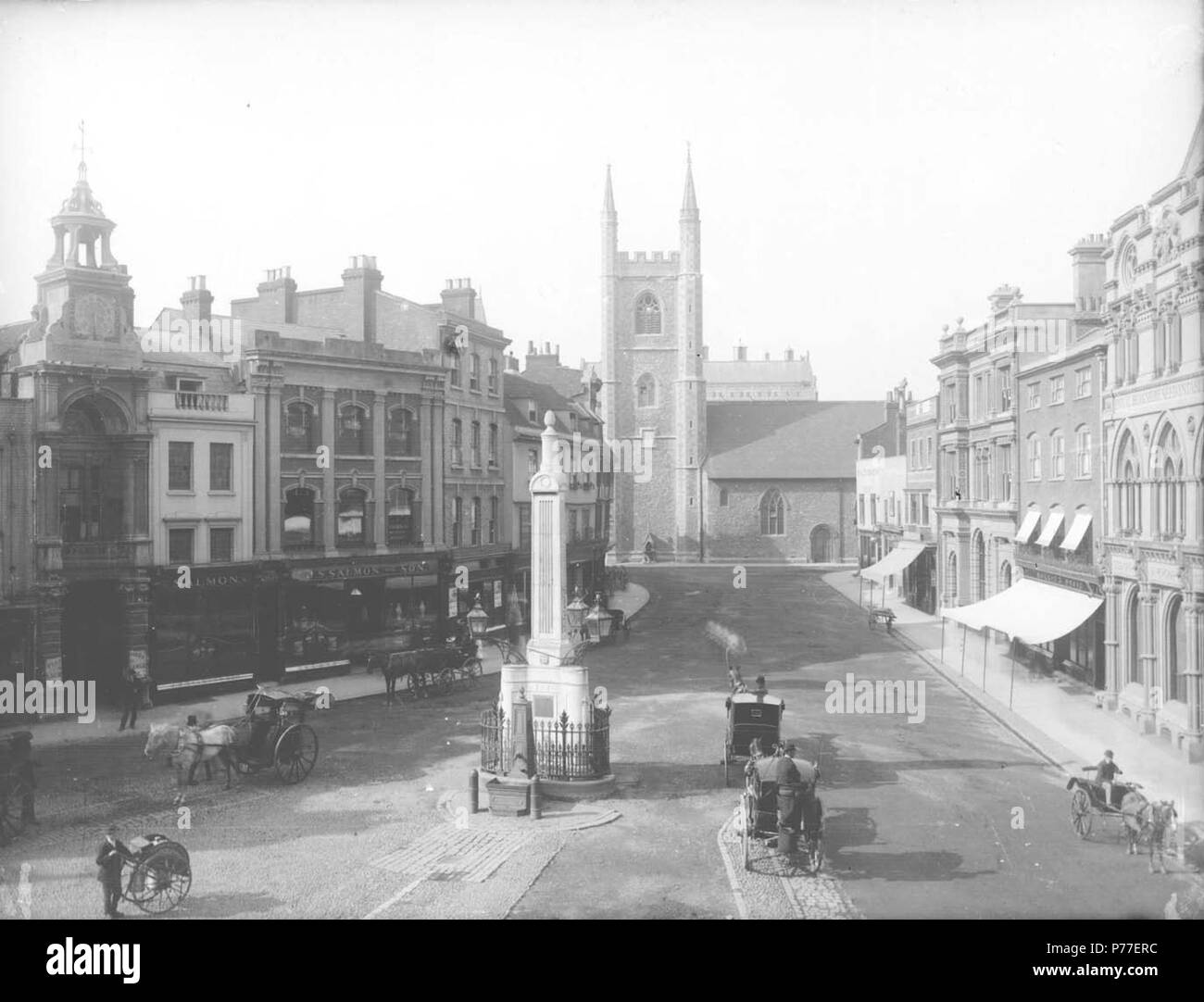 English: Market Place, Reading, looking northwards to St. Laurence's Church, c. 1875. On the west side, the entrance to the Corn Exchange with clock above; Nos. 34 and 33 (Salmon and Son, tea and coffee merchants); No. 32; Nos. 31 and 30; No. 29 (Arthur S. Cooper, wine and spirit merchant). On the east side, Nos. 19 and 18 (Elephant Hotel); No. 17 (Frank Cooksey, estate agent); Nos. 16, 15, 14 and 13 (London and County Bank); No. 12 (Morris and Davis, tailors); Nos. 11 and 9 (Sutton and Sons, seedsmen); and No. 7 ('Reading Mercury' offices). Two cabs wait by the Simeon Obelisk, which has a pum - Stock Image