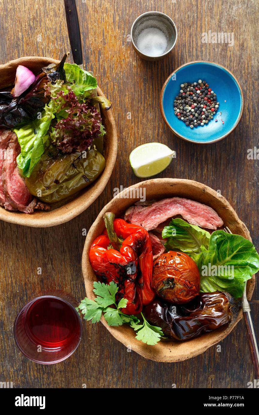 Top view grilled steak and grilled vegetables served in bread plate on wooden table Stock Photo