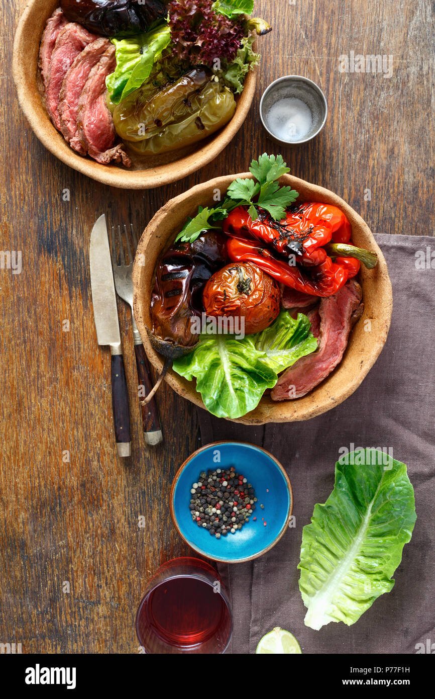 Grilled steak and grilled vegetables served in bread plate on wooden table, top view - Stock Image