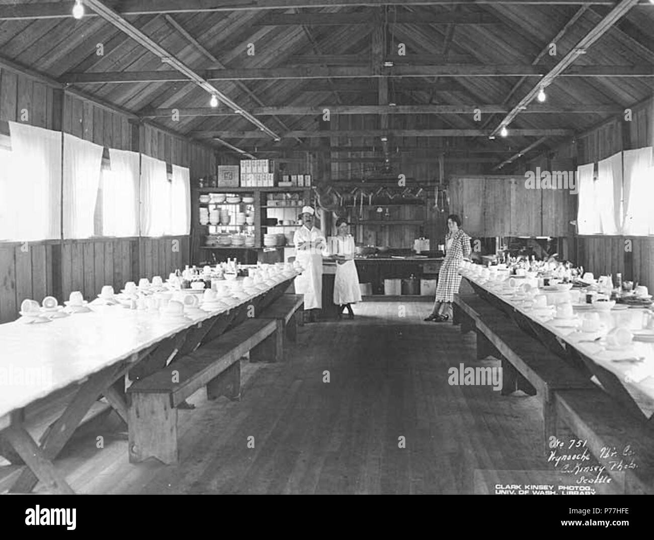 . English: Interior of mess hall with crew, Wynooche Timber Company, Montesano, ca. 1921 . English: Caption on image: Wynooche Tbr Co. C. Kinsey Photo, Seattle. No. 751 PH Coll 516.5232 The Wynooche Timber Company began operations ca. 1913 with headquarters in Hoquiam and logging operations in Montesano. It was named for Wynooche Valley in northeast Grays Harbor County. Wynooche Timber Company was bought out by Schafer Brothers Logging Company ca. 1927. Subjects (LCTGM): Mess halls--Washington (State); Interiors--Washington (State); Table settings & decorations; Cooks; Waitresses--Washington ( - Stock Image