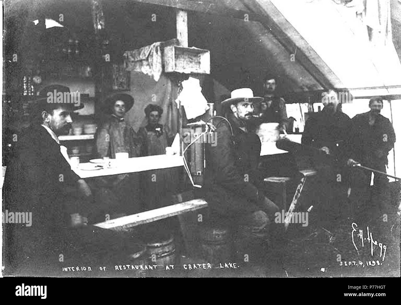 . English: Interior of restaurant, Crater Lake, British Columbia, September 4, 1898. English: Shows men sitting at table inside permanent tent structure . Caption on image: 'Interior of restaurant at Crater Lake. Sept. 4, 1898' Klondike Gold Rush. Subjects (LCTGM): Restaurants--British Columbia Subjects (LCSH): Chilkoot Trail; Trails--British Columbia  . 1898 6 Interior of restaurant, Crater Lake, British Columbia, September 4, 1898 (HEGG 290) - Stock Image