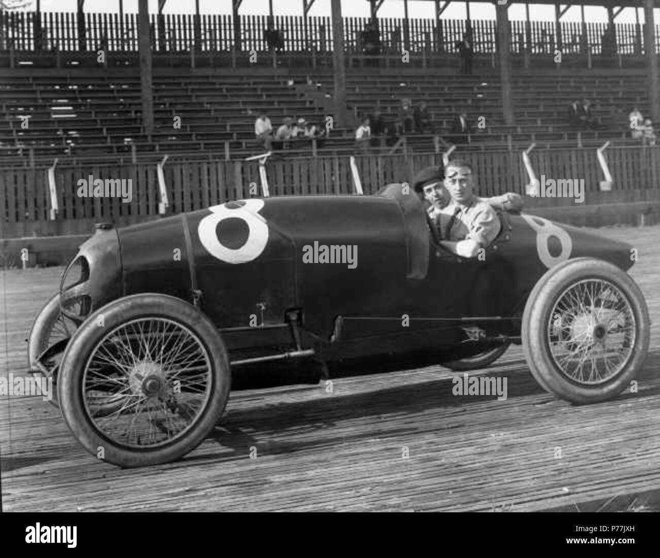 English: Auto racer Art Klein at the Tacoma Speedway. He is aboard the #8 Frontenac along with his riding mechanic, or 'mechanician,' S. McGarigle. Mr. Klein drove one of the two Frontenacs in the 1920 225-mile race at the Tacoma Speedway; the other was helmed by Chicago millionaire Joe Boyer, Jr. The Speedway had been spruced up with large new grandstand (shown above), fences, pits, water tower, renewed board track and three automobile entrances for spectators. Top drivers including Cliff Durant, Ralph DePalma, Tommy Milton, Roscoe Sarles and Ralph Mulford made the long trek to Washington to  - Stock Image