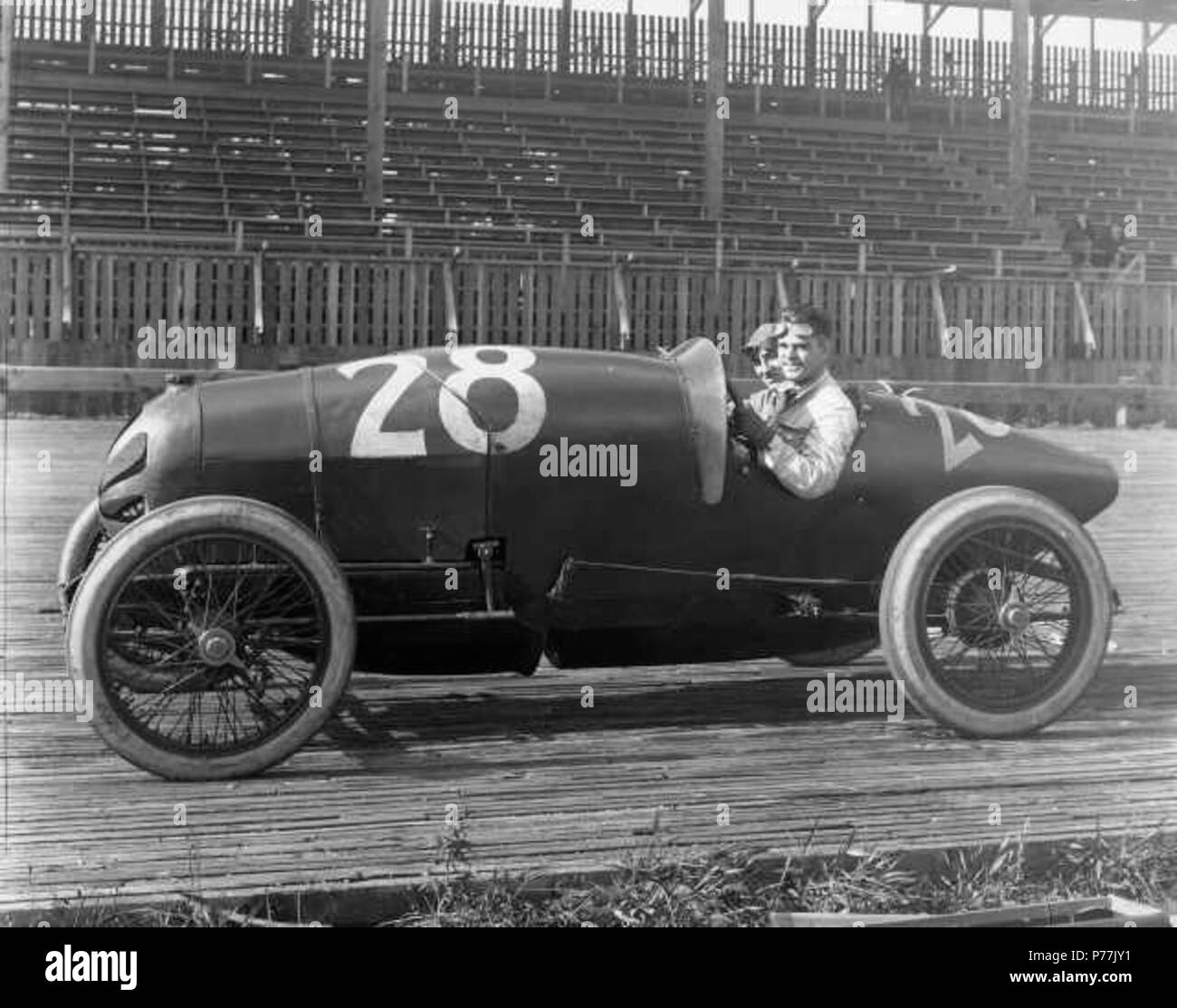 English: Seattle driver Joe Thomas and his 'mechanician,' believed to be  Marcel Treyvoux, smile for the cameraman while seated in their #28 car,  thought to be a Frontenac. The duo were to