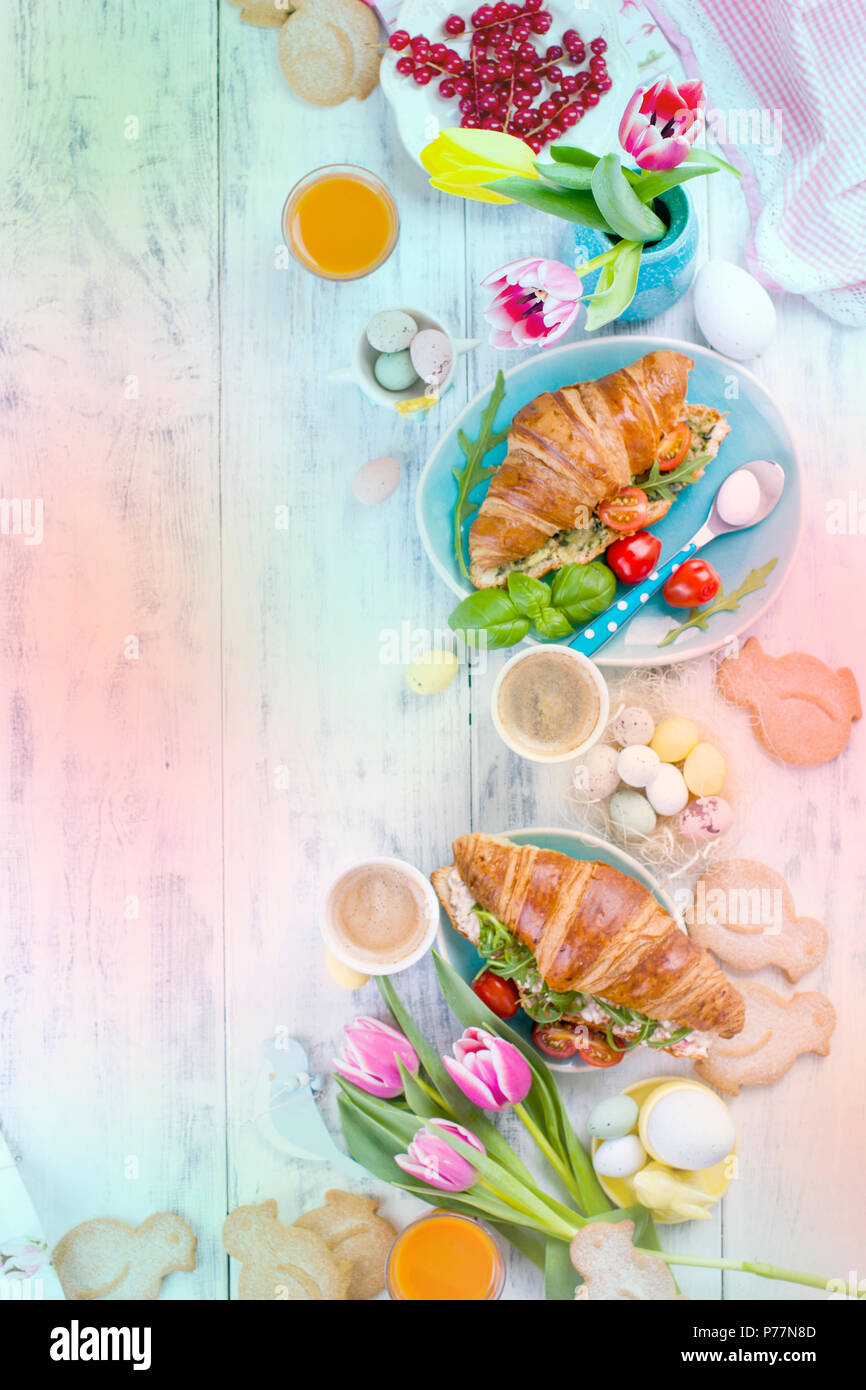 Easter breakfast. A family breakfast of croissants with rocket salad and cheese and aromatic coffee. Fresh tulips of pink color and eggs of different colors and Easter decor. Free space for text - Stock Image