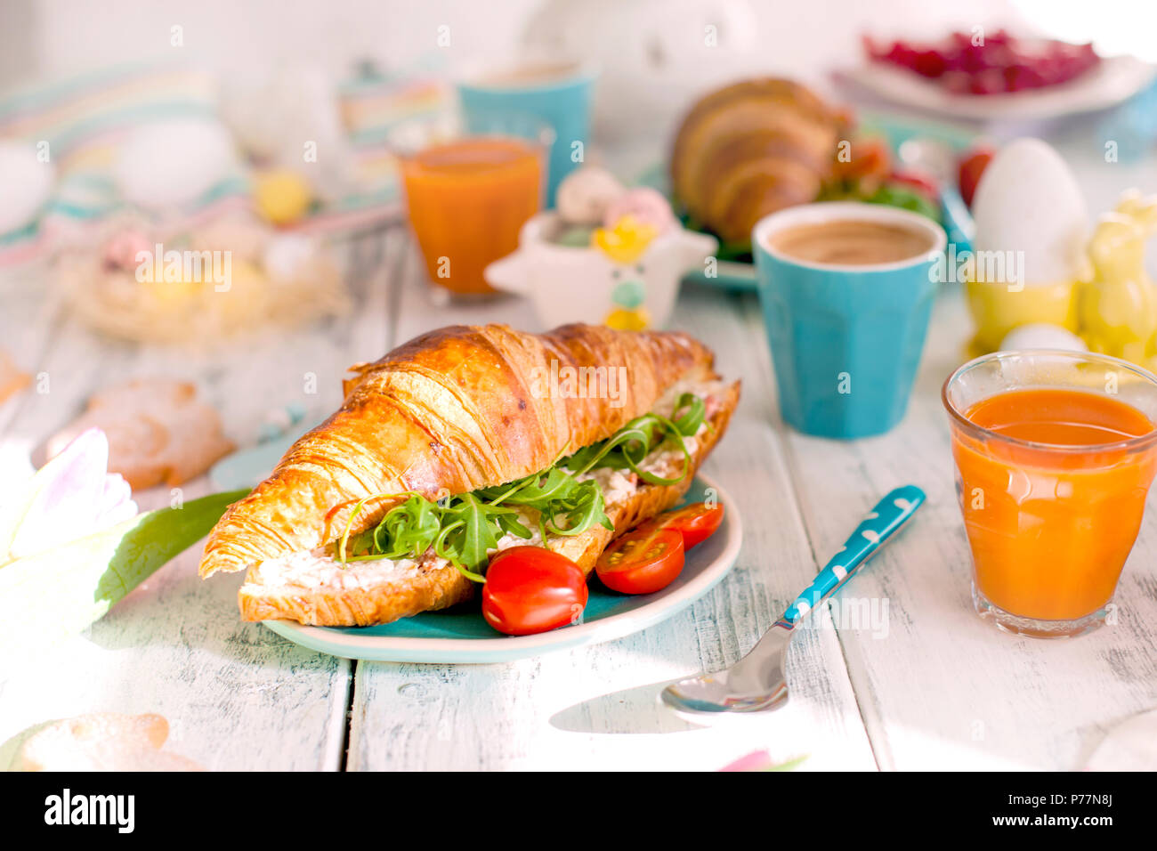 A family breakfast of croissants with rocket salad and cheese and aromatic coffee. Fresh tulips of pink color and eggs of different colors and Easter decor, ceramic rabbits. Free space for text. - Stock Image