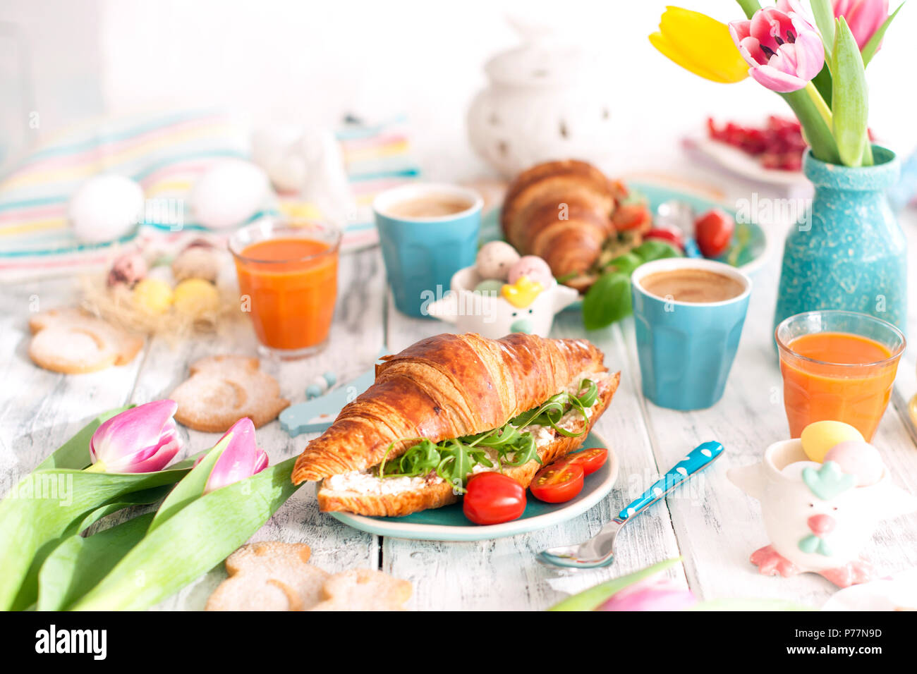 Background with different colors. A family breakfast of croissants with rocket and cheese and aromatic coffee, eggs of different colors, bright dishes and Easter decor, ceramic rabbits - Stock Image