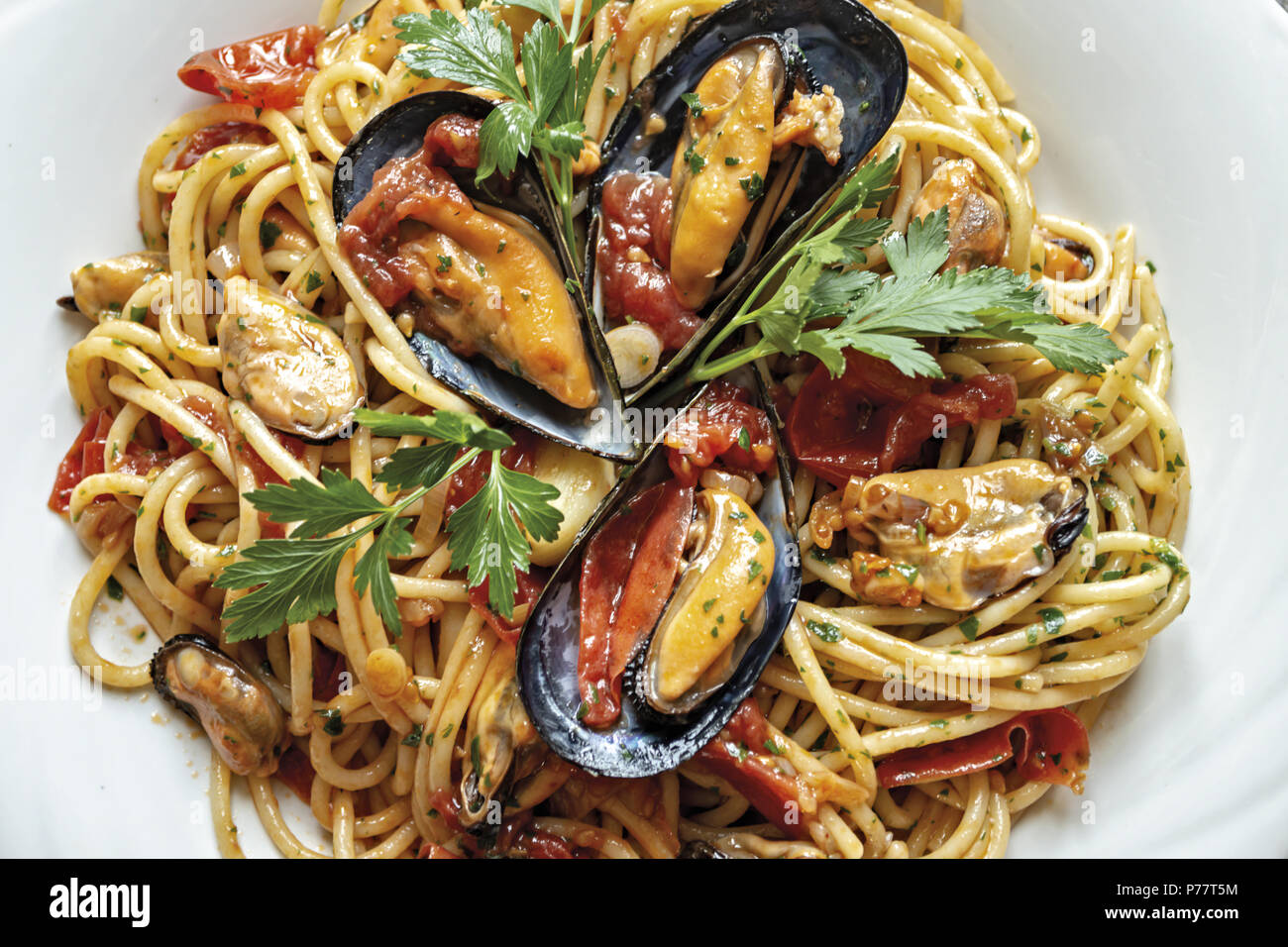 spaghetti pasta with mussels tomato and parsley - Stock Image