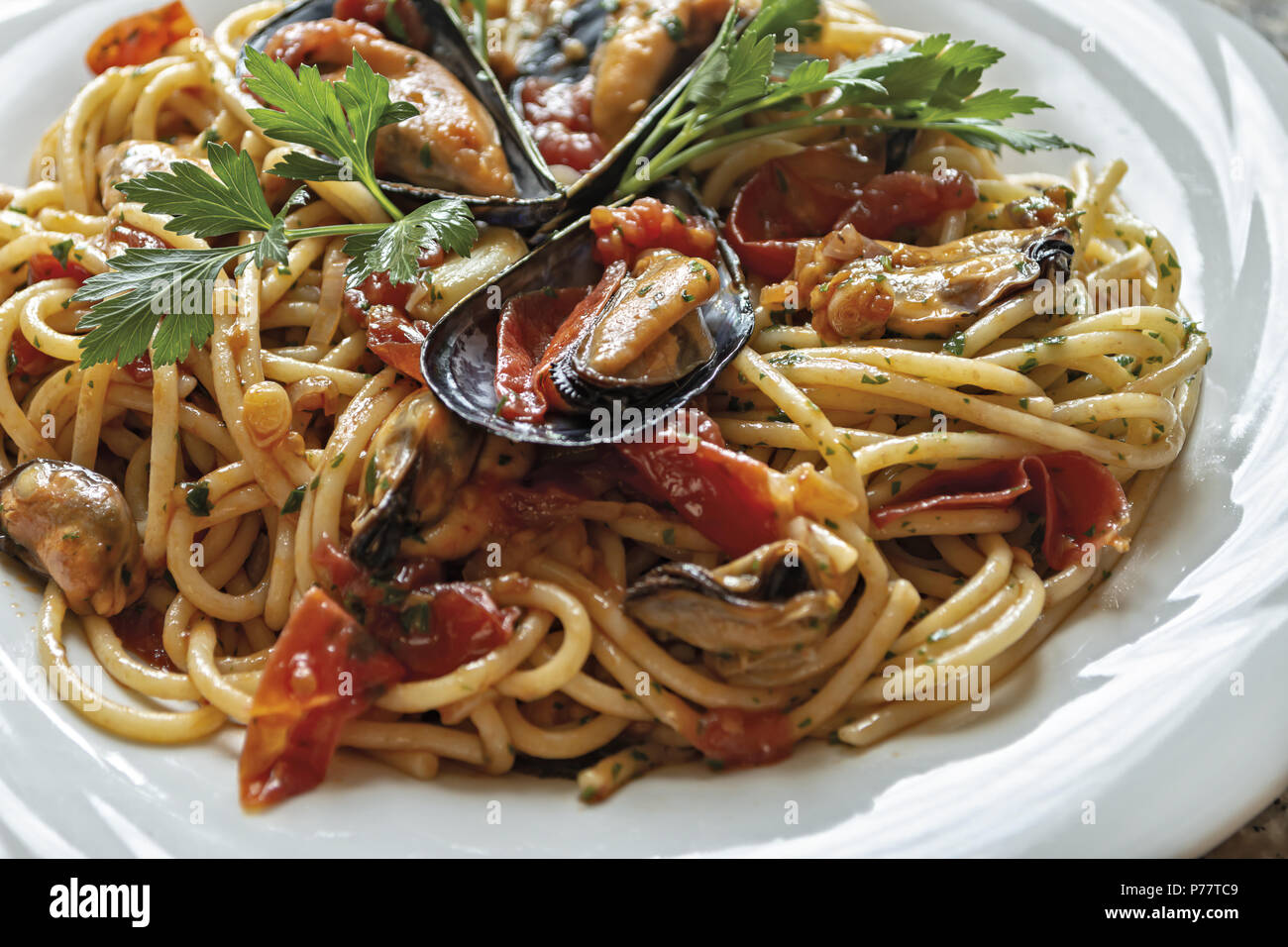 spaghetti pasta with mussels tomato and parsley 4 - Stock Image