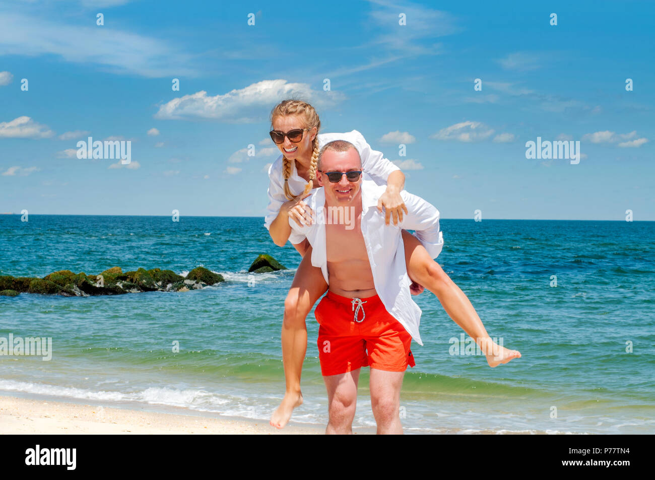 Happy couple in love on beach summer vacations. Young man giving piggyback ride to woman on beach. - Stock Image