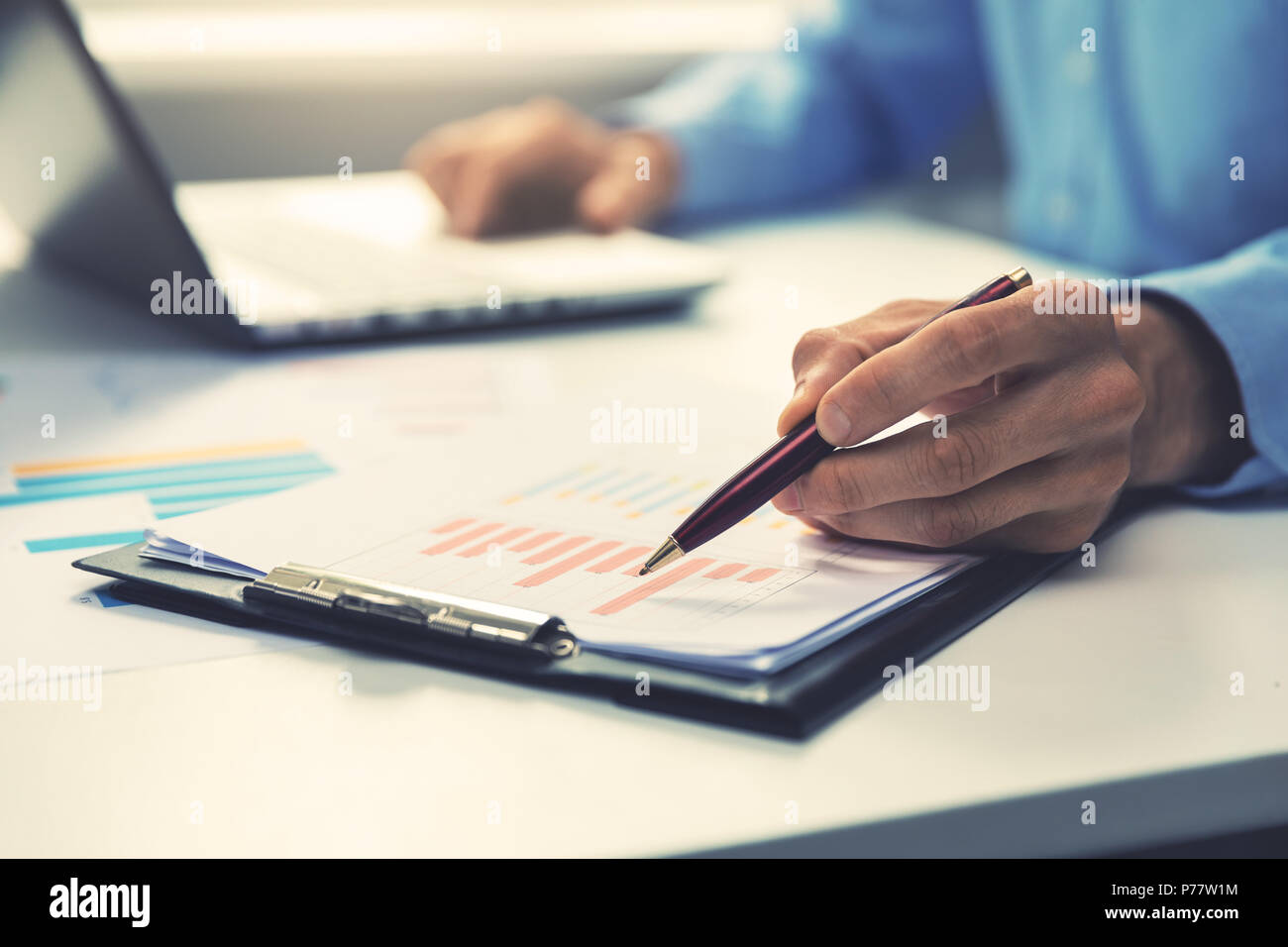 businessman pointing with pen on annual business report chart - Stock Image