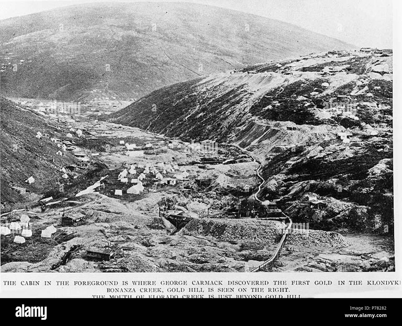 . English: Mining operations in the vicinity of Bonanza Creek and Eldorado Creek, Yukon Territory, ca. 1898. English: Caption on image: 'Cabin in the foreground is where George Carmack discovered the first gold in the Klondyke. Bonanza Creek, Gold Hill is seen on the right. The mouth of Eldorado Creek is just beyond Gold Hill' Klondike Gold Rush. Subjects (LCTGM): Mining--Yukon; Log cabins--Yukon--Bonanza Creek Subjects (LCSH): Bonanza Creek (Yukon); Eldorado Creek (Yukon); Gold Hill (Yukon); Yukon--Gold discoveries  . circa 1898 9 Mining operations in the vicinity of Bonanza Creek and Eldorad - Stock Image
