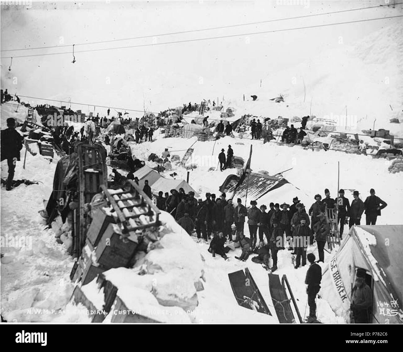 . English: North-West Mounted Police and Canadian custom house on Chilkoot summit, Alaska, ca. 1898. English: Shows Klondikers with supply caches . Caption on image: 'N.W.M.P. and Canadian custom house on Chilkoot summit' Original photograph by Eric A. Hegg 211; copied by Webster and Stevens 164.A . Klondike Gold Rush. Subjects (LCTGM): Sleds & sleighs--Alaska--Chilkoot Pass; Customhouses--Alaska--Chilkoot Pass Subjects (LCSH): Chilkoot Pass (Alaska); Mountain passes--Alaska; Chilkoot Trail; Trails--Alaska; North West Mounted Police (Canada)  . circa 1898 10 North-West Mounted Police and Canad - Stock Image