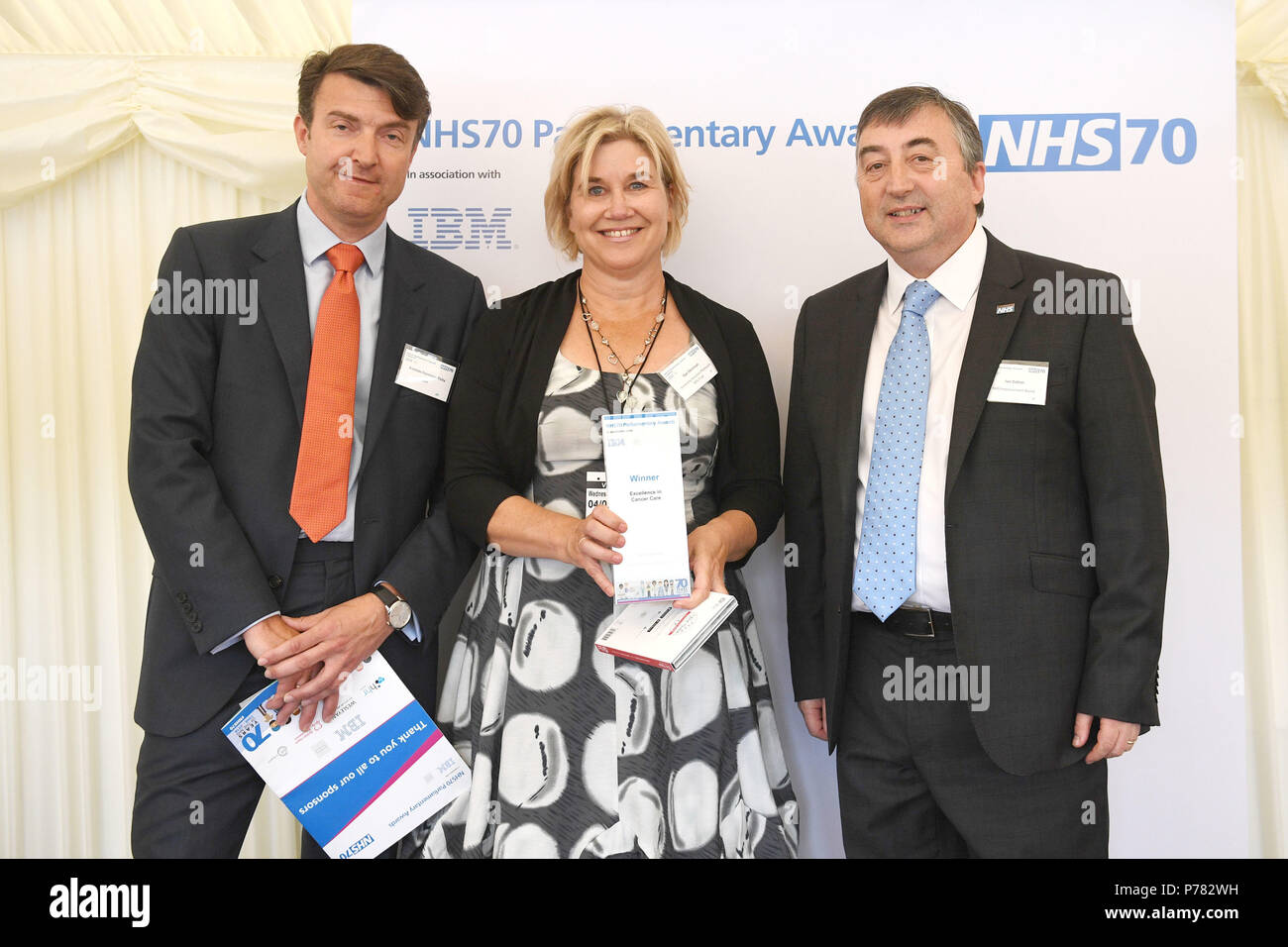 Sian Dennison receives her Excellence in Cancer care Award from Andreas Haimbock-Tichy (left) and Ian Dalton (right) during the NHS70 parliamentary awards for the 70th anniversary of the NHS at the House of Commons in Westminster, London. - Stock Image