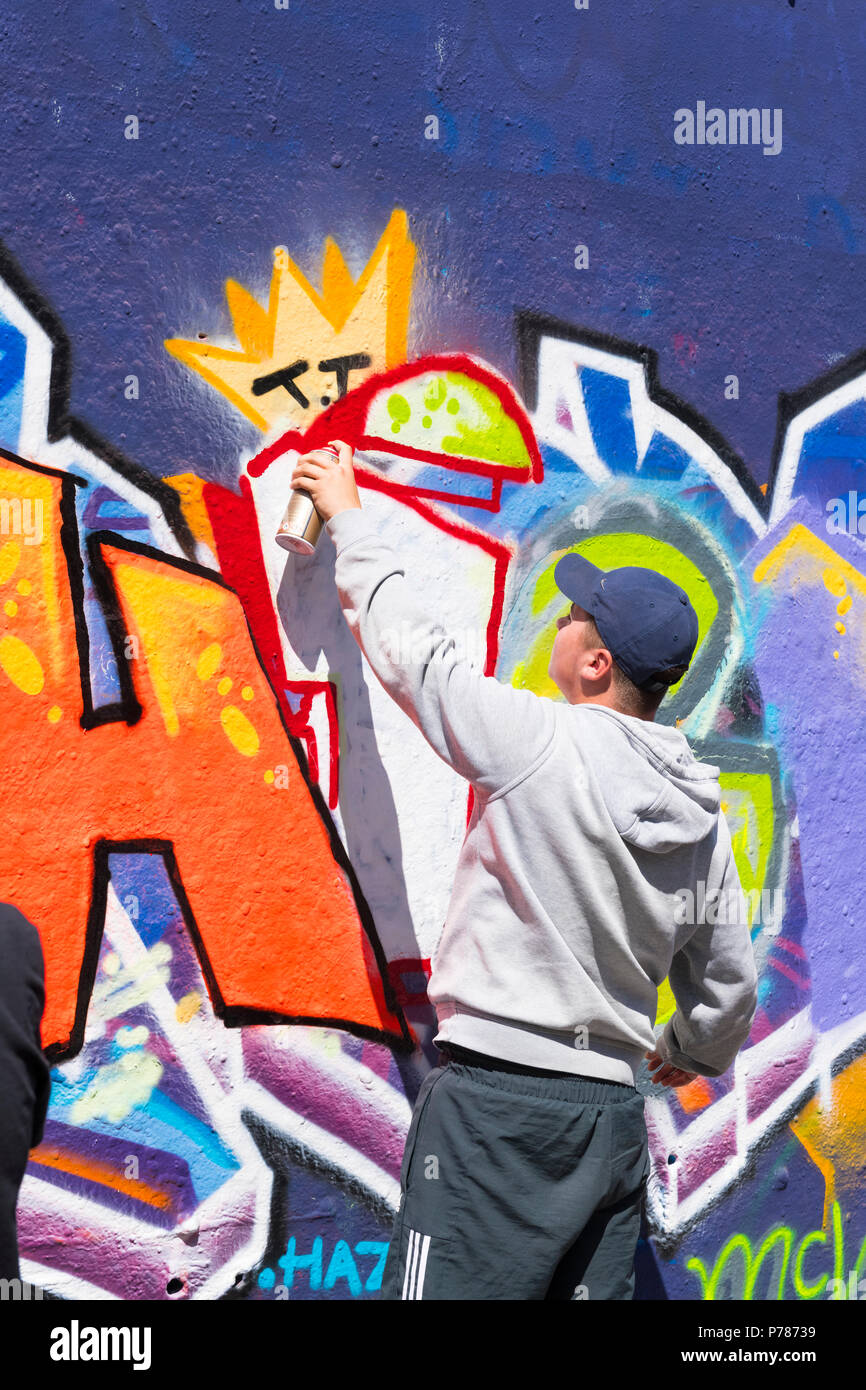 London Waterloo Leake Street art college group pupil boy man learning graffiti spray paint painting red outline letter hoodie baseball cap hat - Stock Image