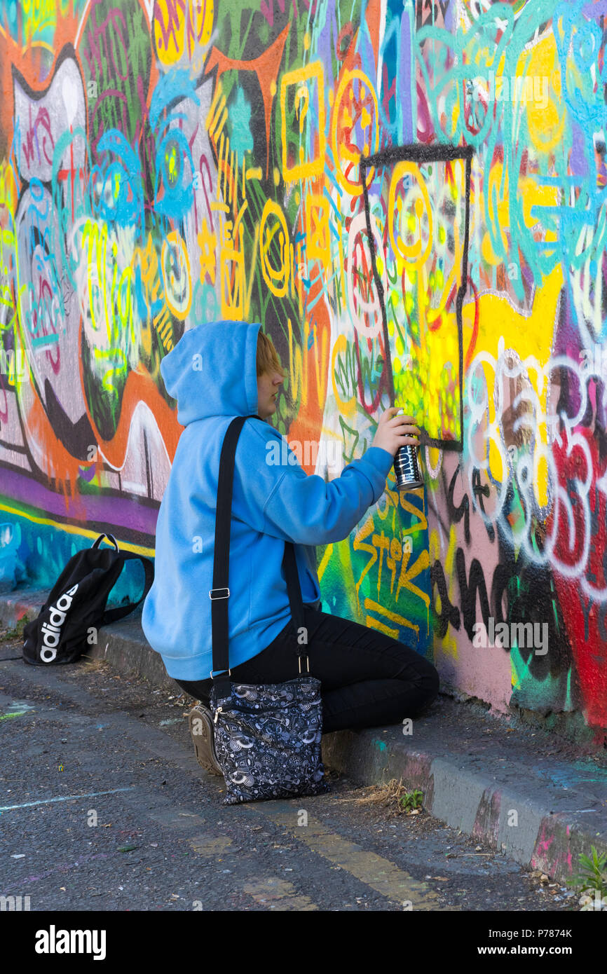 London Waterloo Leake Street art college group pupil pretty blond girl blue hoodie learning graffiti spray paint painting abstract handbag road kerb - Stock Image