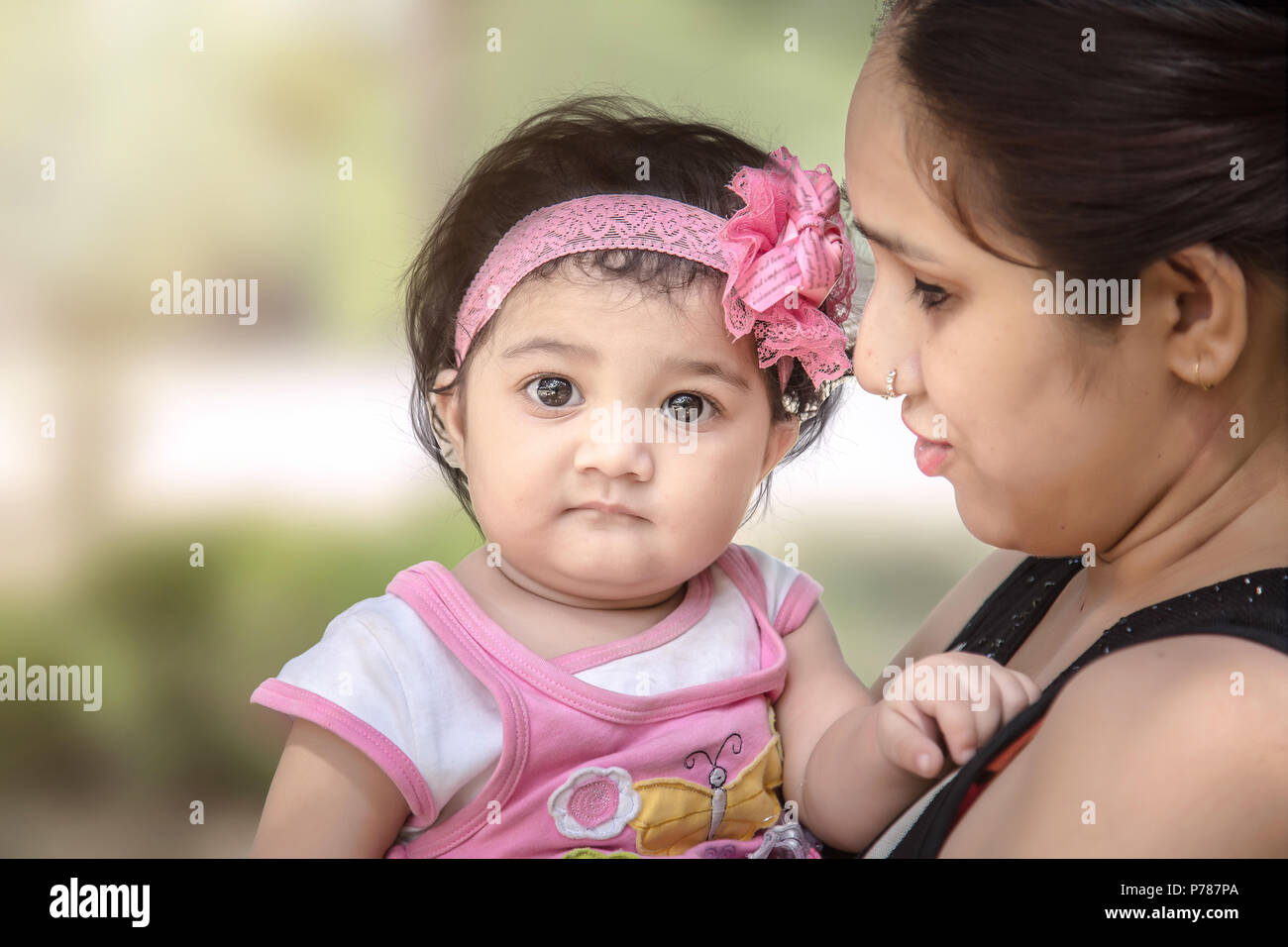 Sad Indian/Asian baby girl in mother arm. - Stock Image