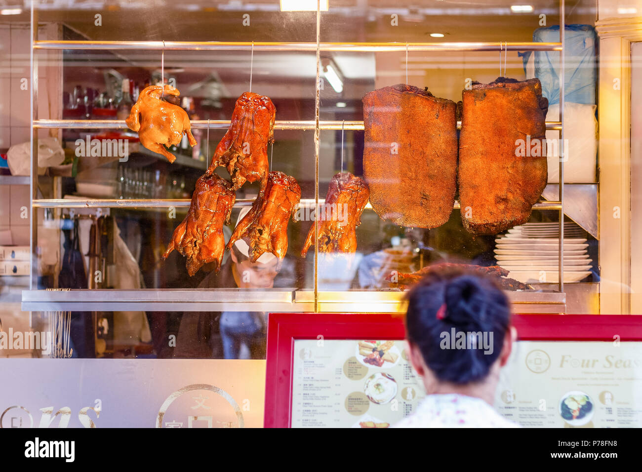 London, UK - June 22, 2018 - A tourist is reading the menu outside Four Seasons restaurant, famous for the crispy duck, in London Chinatown - Stock Image