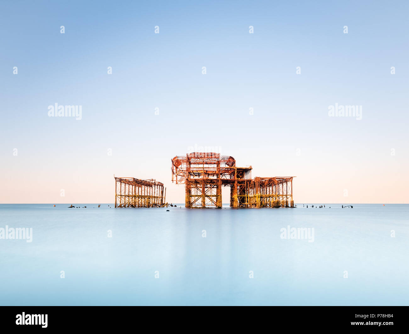 Minimalistic West Pier in Brighton, East Sussex, at sunrise and reflected in a calm sea with beautiful pastel shades in a cloudless sky - Stock Image