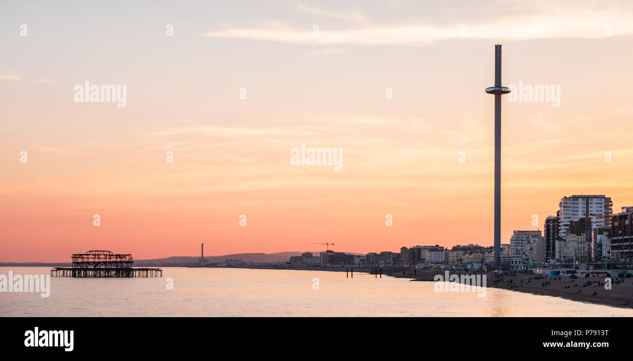 British Airways i360 and West Pier, Brighton, East Sussex, including the seafront at sunset with intense orange and yellow sky - Stock Image