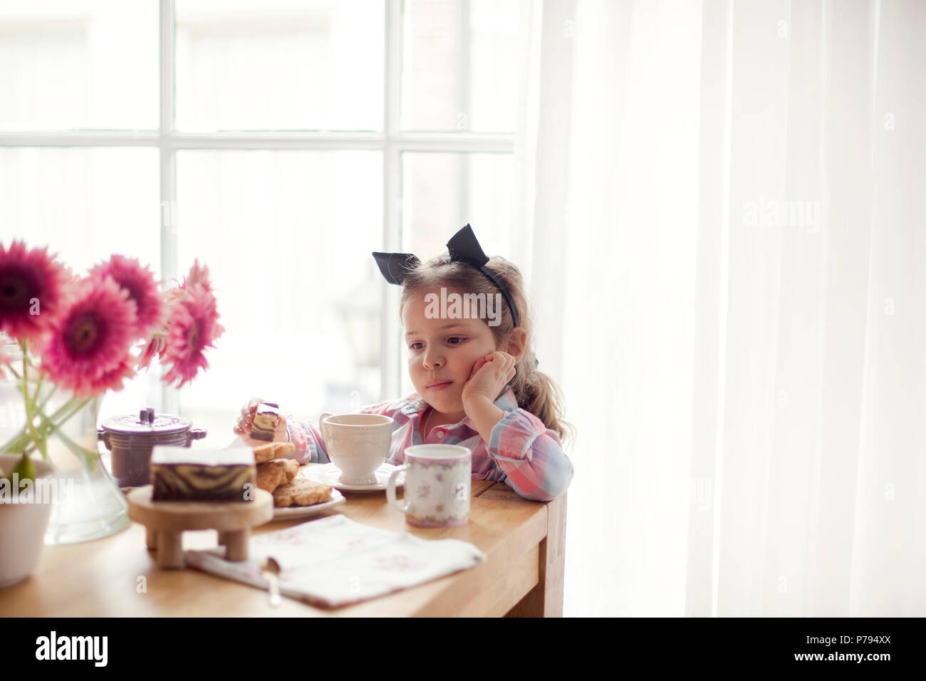 A little girl at the table is eating breakfast by the window. Good morning. Copy space - Stock Image