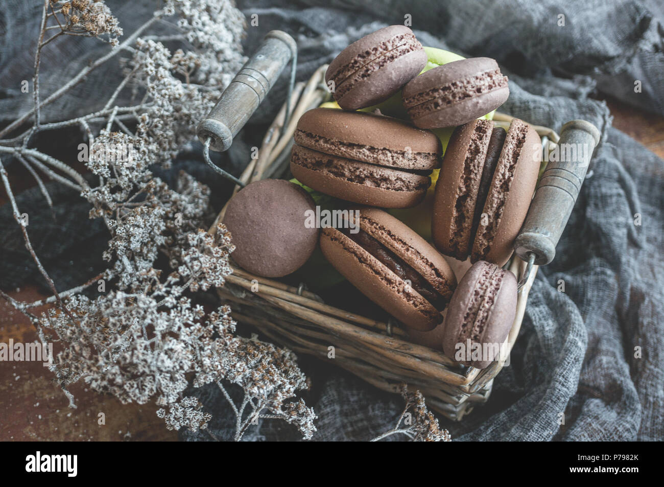 Freshly baked macaroons in wicker basket with handles with small white flowers on wooden background. Selective focus. - Stock Image