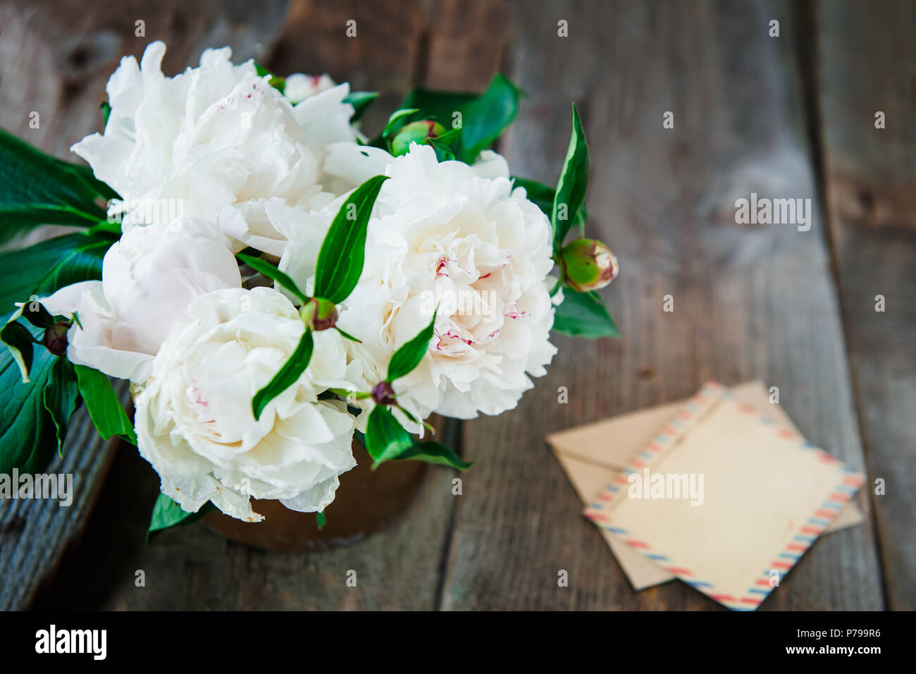 Top view white peony flowers bouquet blank greeting card and craft top view white peony flowers bouquet blank greeting card and craft paper envelope on the old wooden rustic table background postcard mock up creati izmirmasajfo