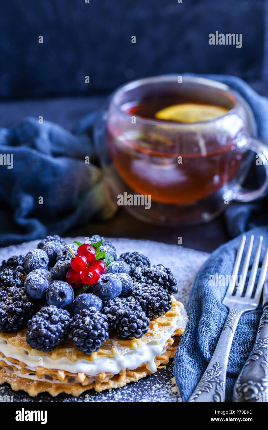 homemade waffles with blueberries and blackberries, powdered sugar on a stone plate with fruit. Shallow depth of field. - Stock Image