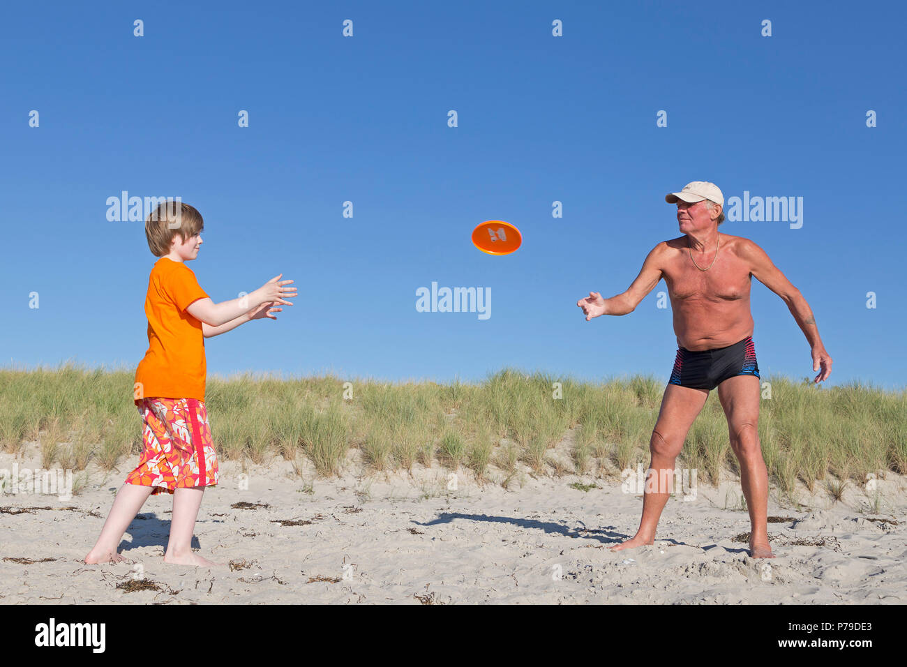 grandpa and grandson playing with a frisbee disc at the beach, Wustrow, Fischland, Mecklenburg-West Pomerania, Germany - Stock Image