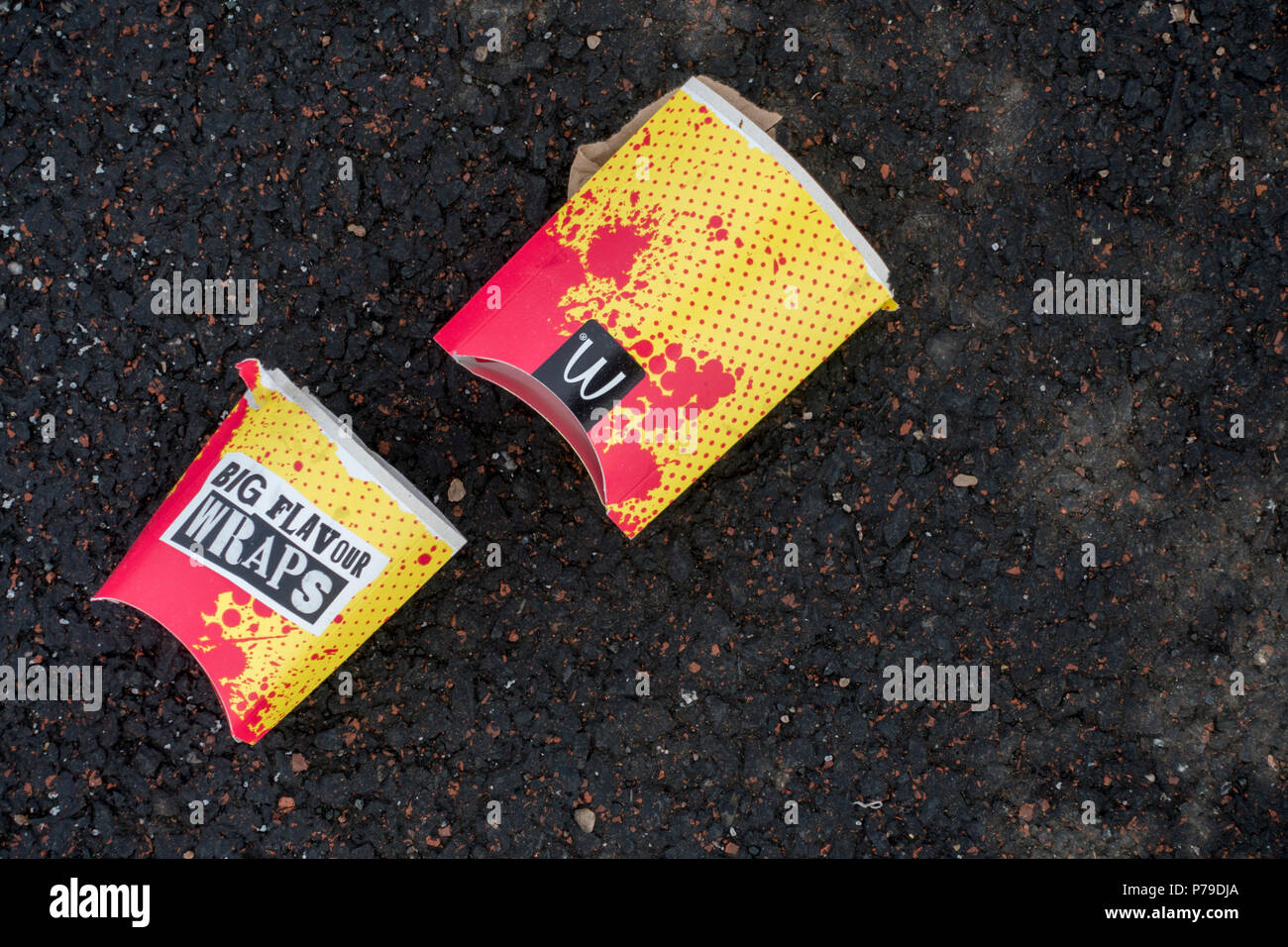 Crushed McDonalds cardboard food and drink packaging littering the ground - Stock Image